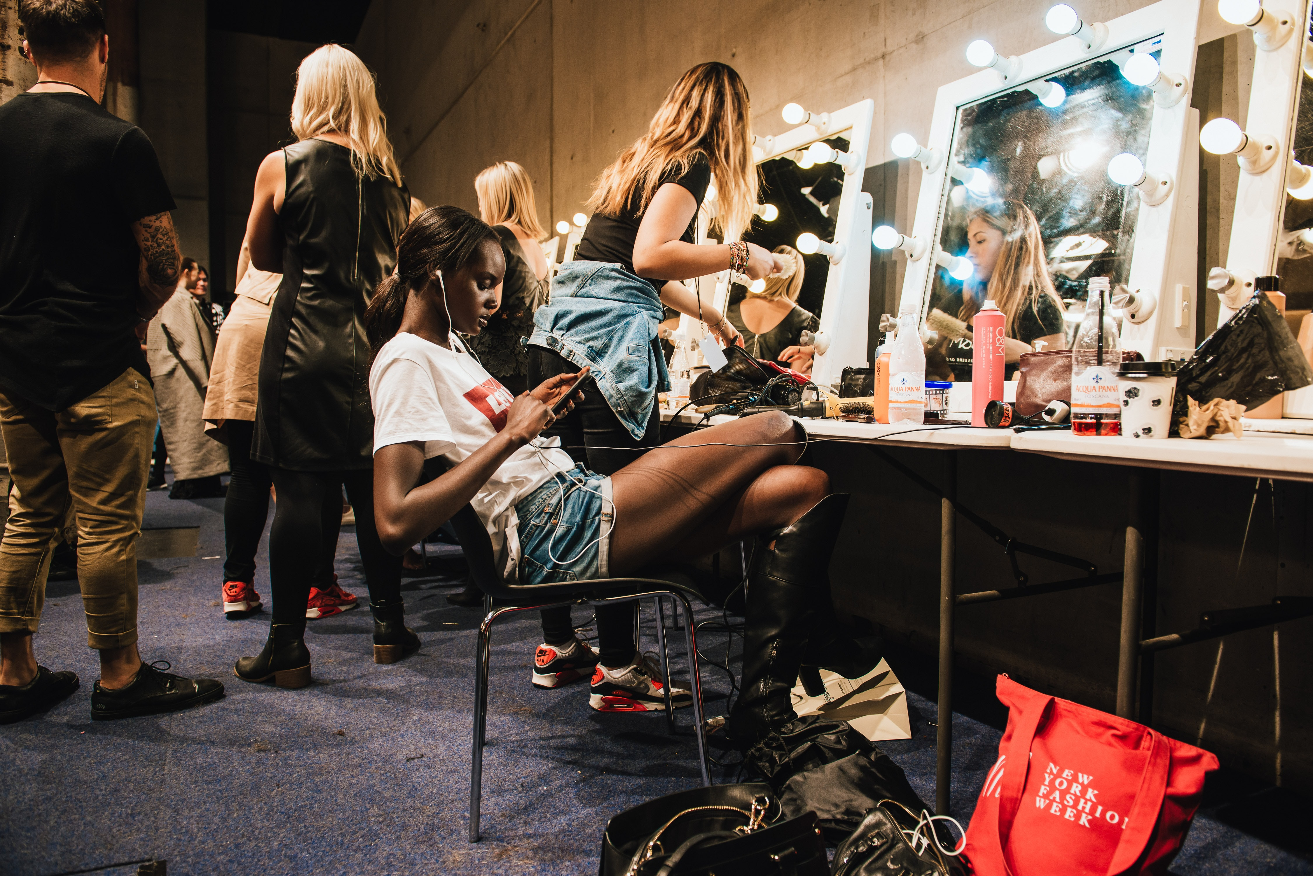 Models backstage at a runway show getting ready and relaxing