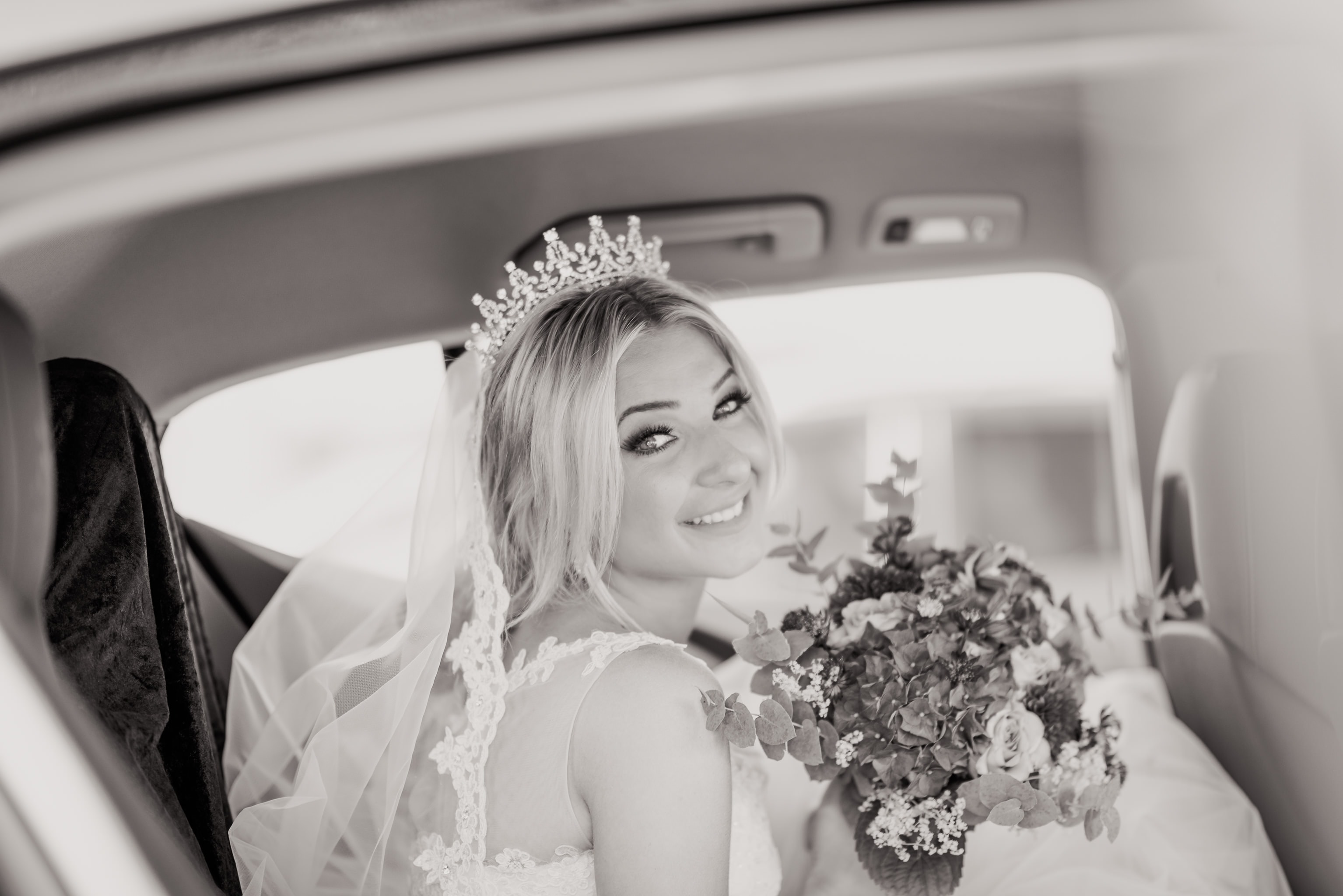 A bride holding flowers while looking at the camera, getting into a vehicle.