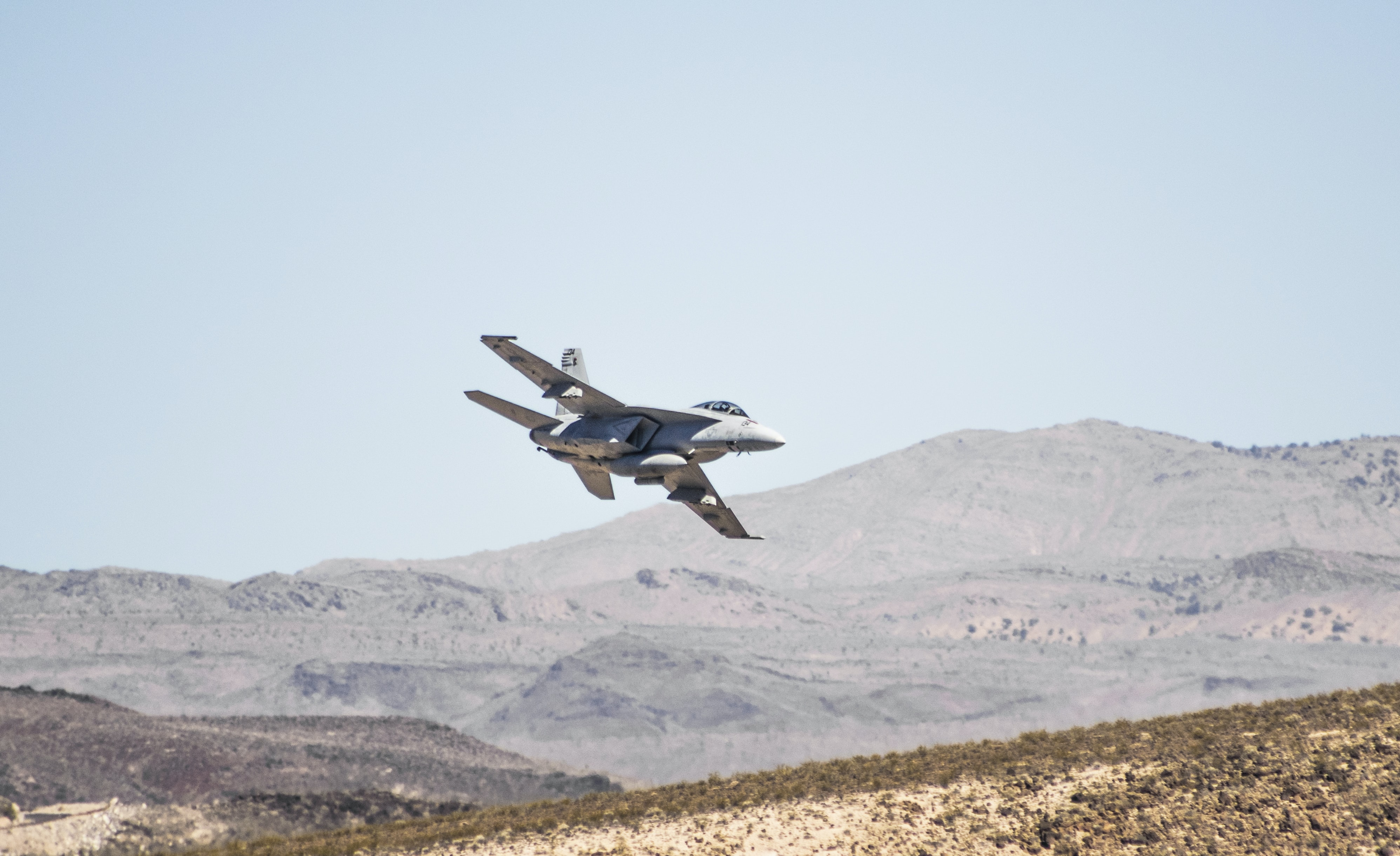 Military airplane flies over the desert
