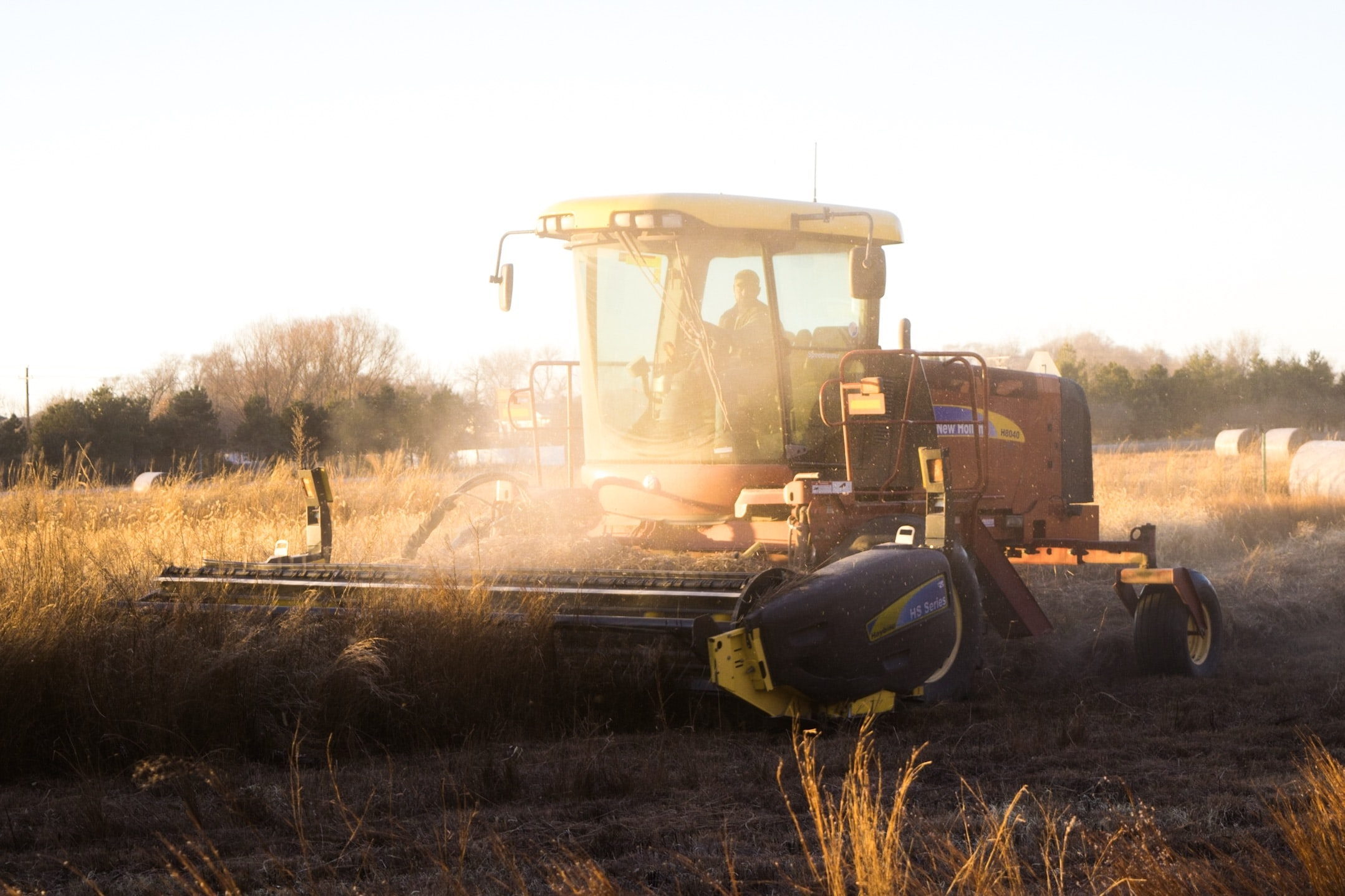 A farmer in a tractor, clearing wheat during sunset in Lincoln
