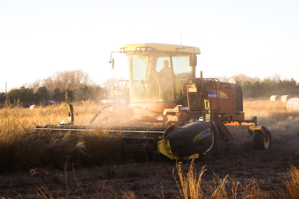 person riding brown combine harvester during daytime