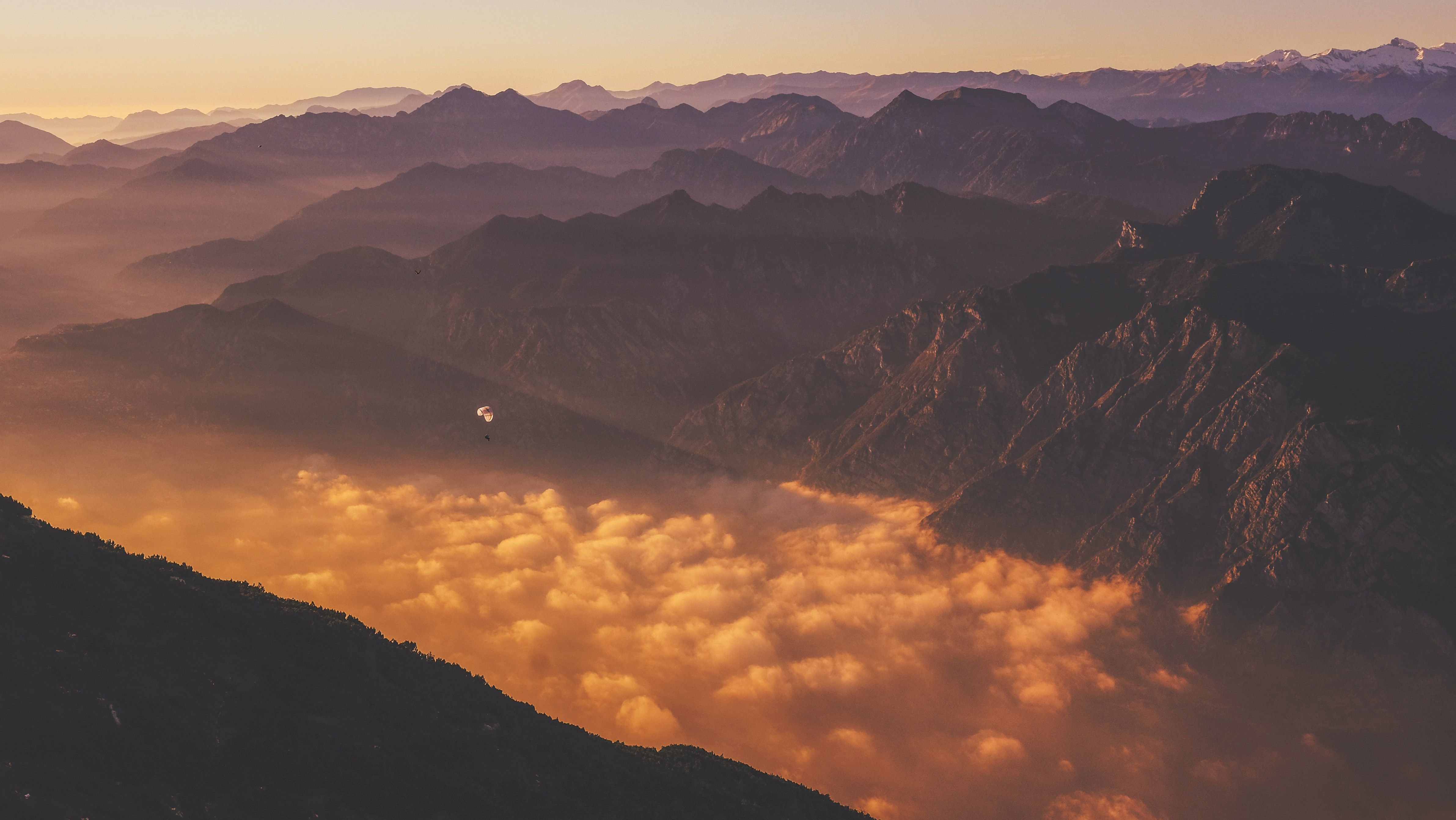 A paraglider over clouds obscuring the bottom of a mountain valley during sunset