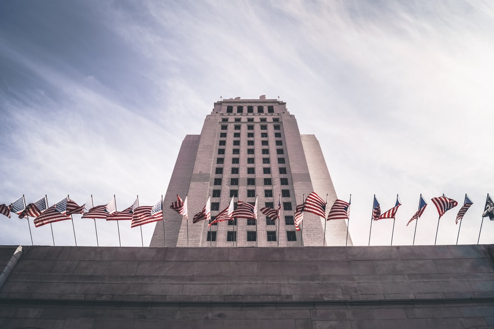 low angle view photography of U.S.A flags on concrete building