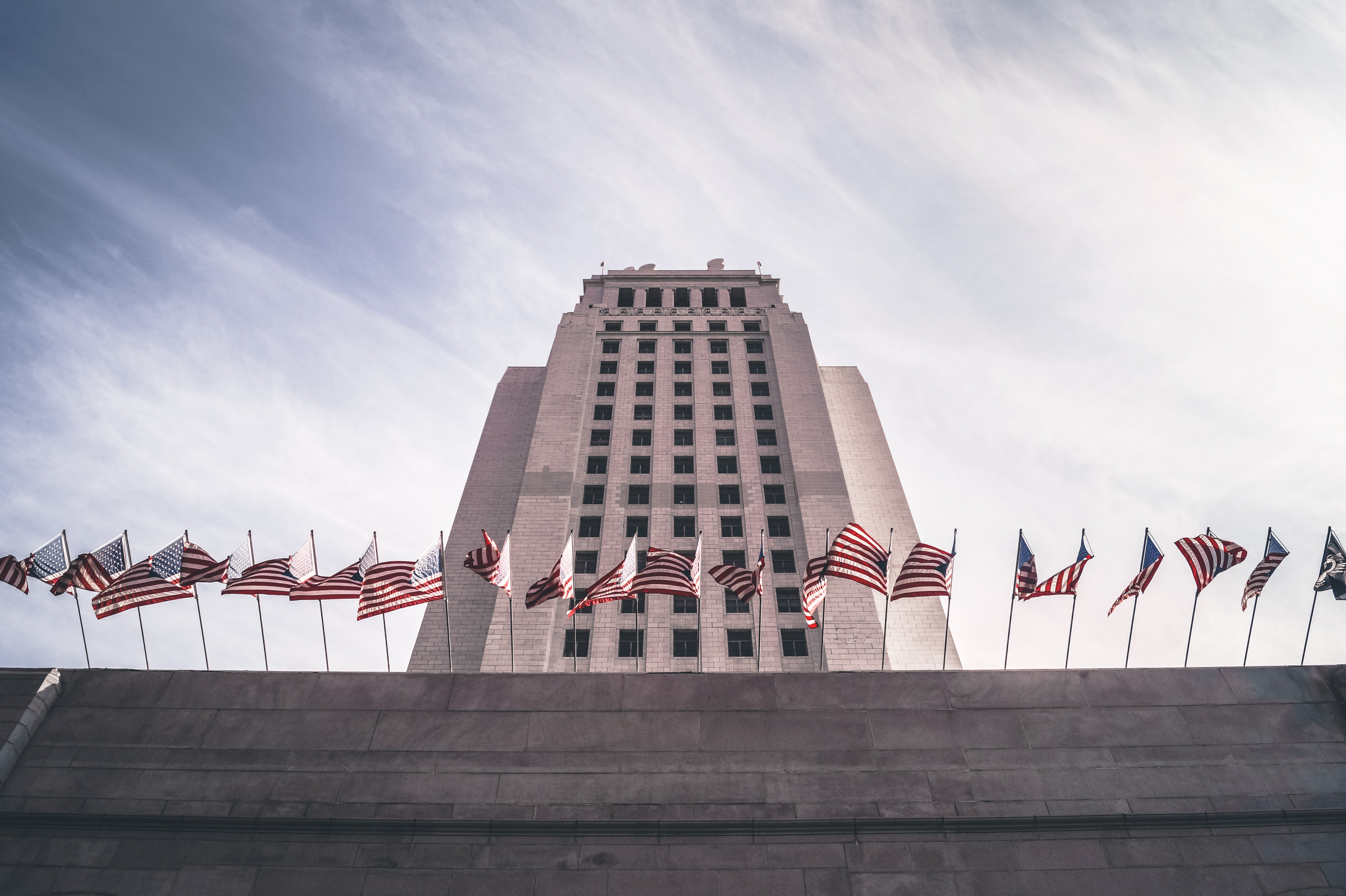 A long row of American flags on a concrete ledge near Los Angeles City Hall