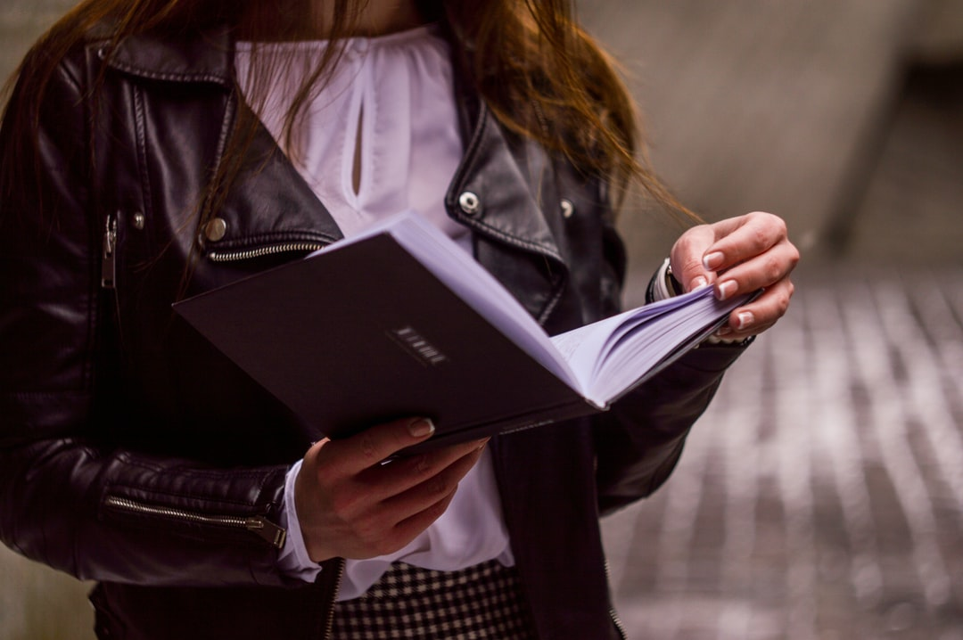A woman in a leather jacket and white blouse holds an open book, reading