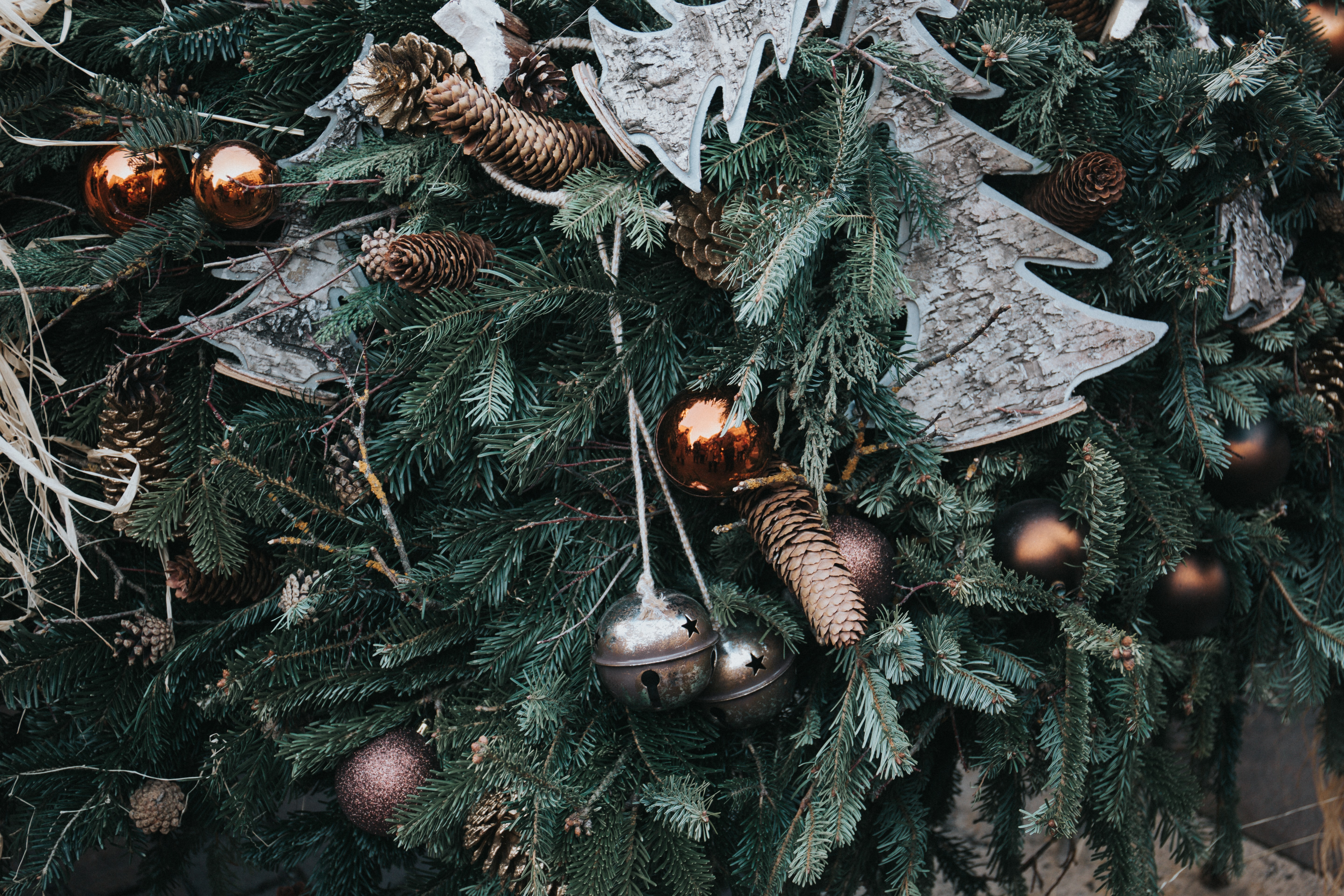 Gold, silver, and white ornaments hung on an evergreen tree