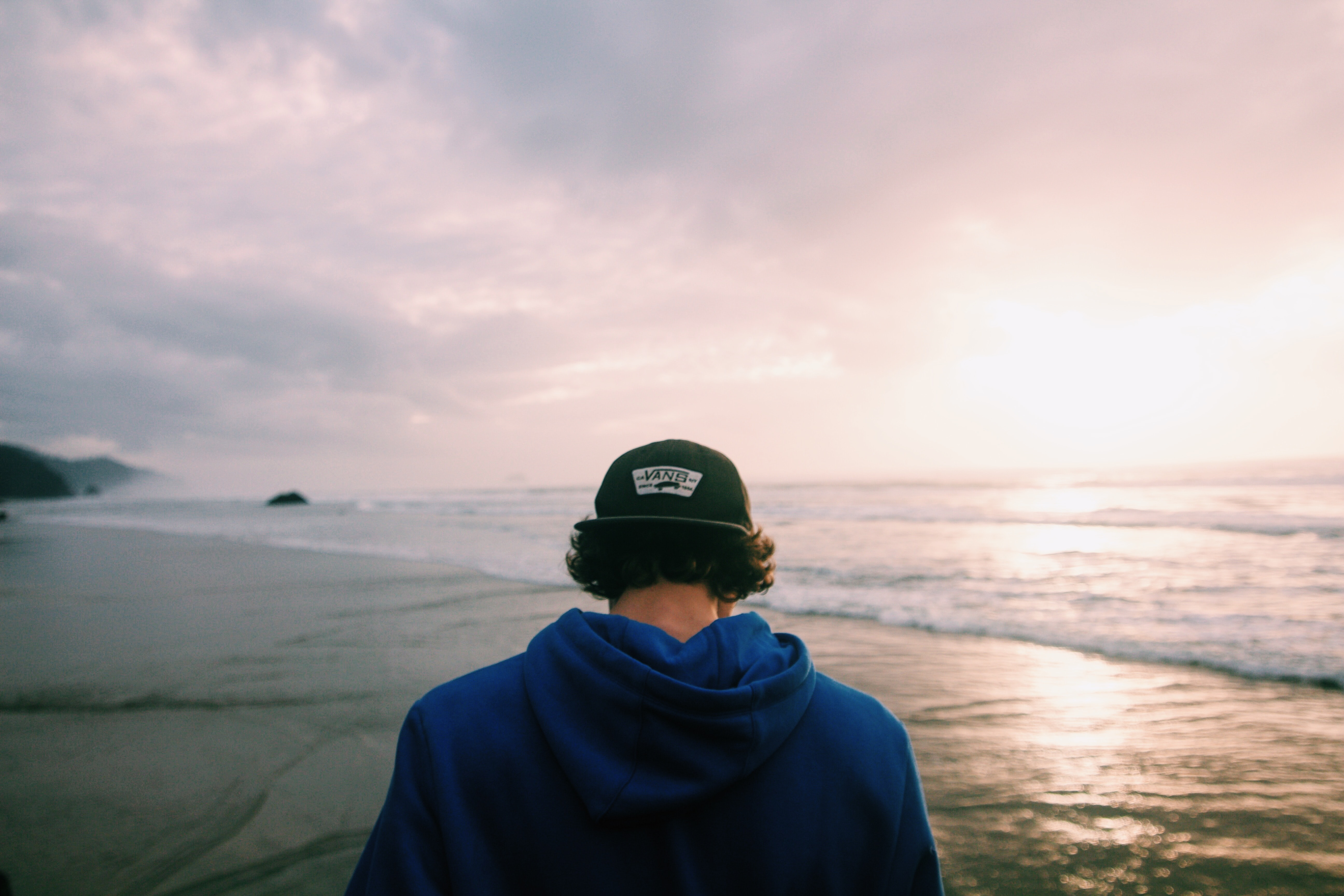 Walking behind a man in a baseball hat on the ocean shore
