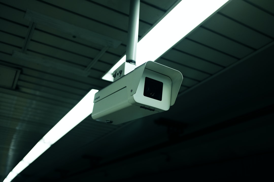 White surveillance camera monitoring a dark space with lined ceilings and overhead lights
