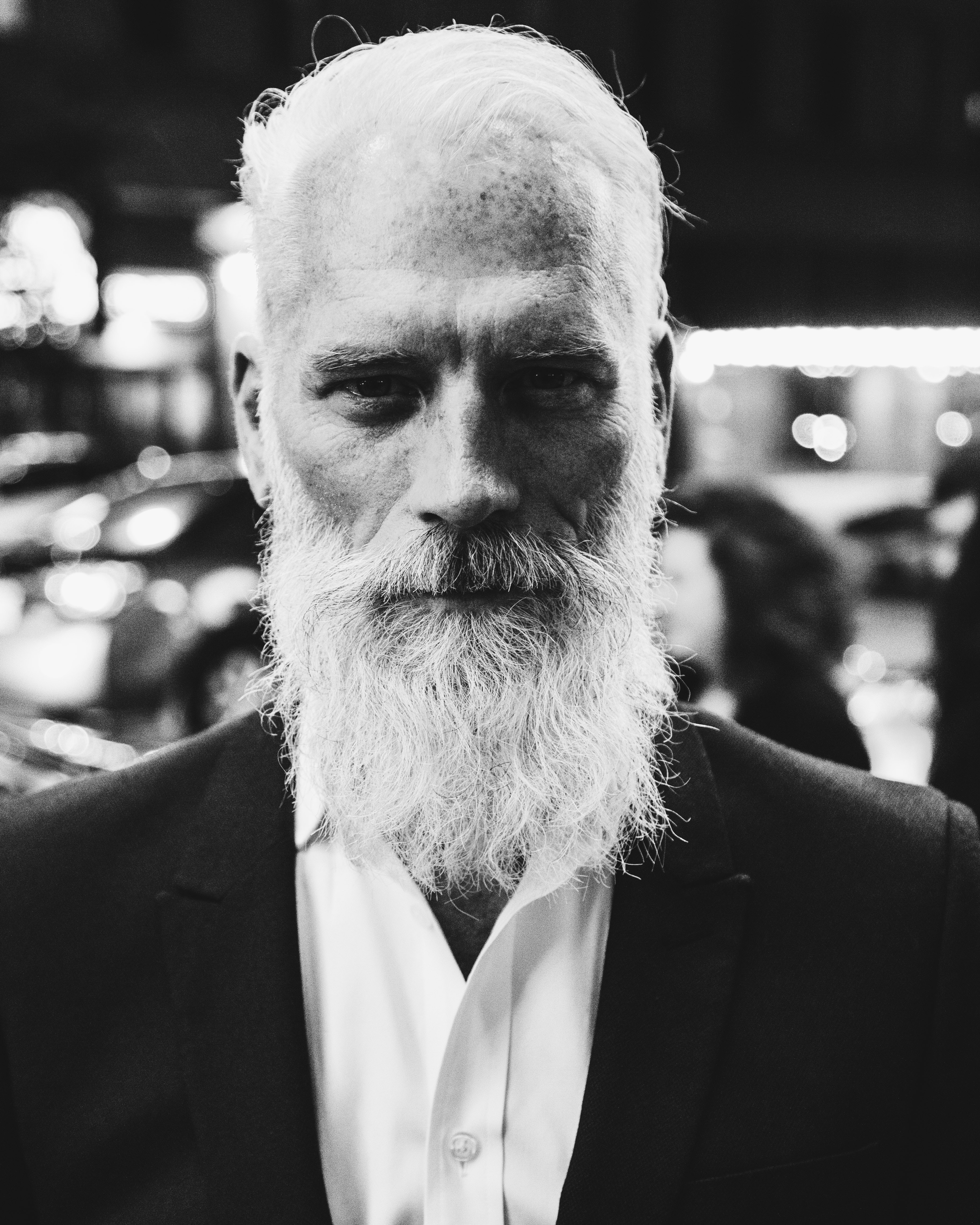 Black and white shot of attractive older man with white beard in blazer and shirt, Toronto