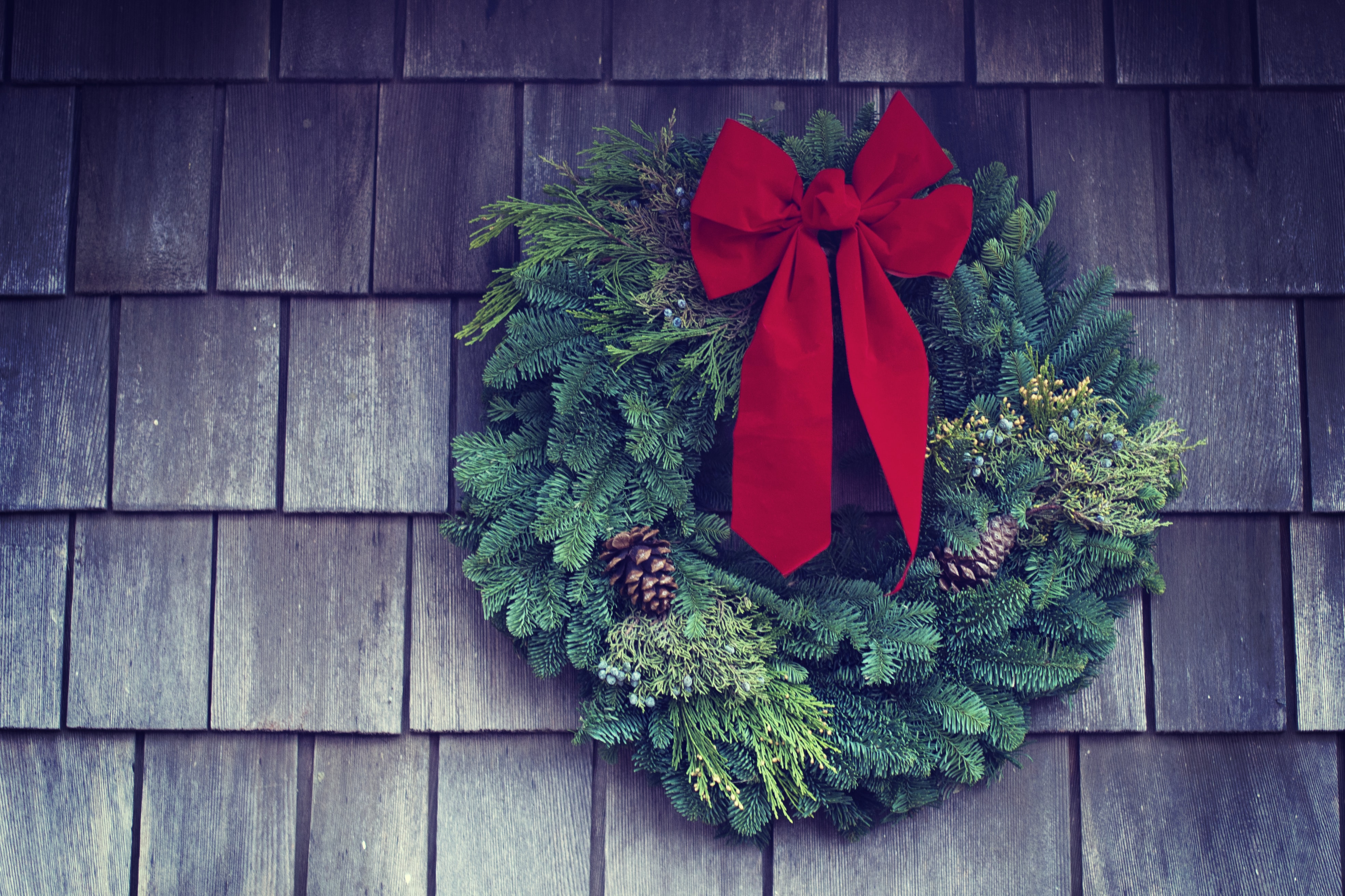 A Christmas wreath with a red bow and pinecones hanging on the side of a shingled house