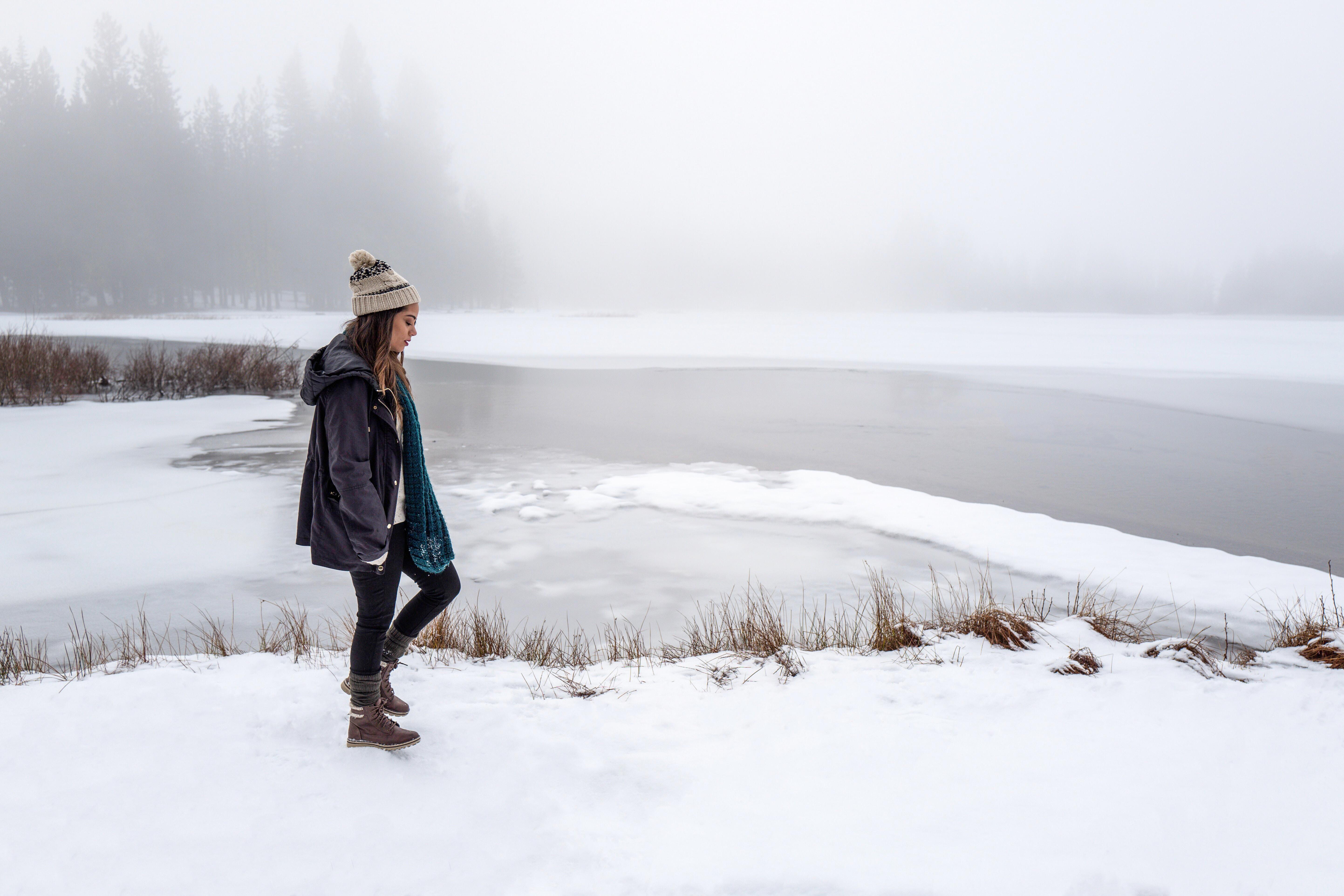 Woman walking through snow along a frozen lake