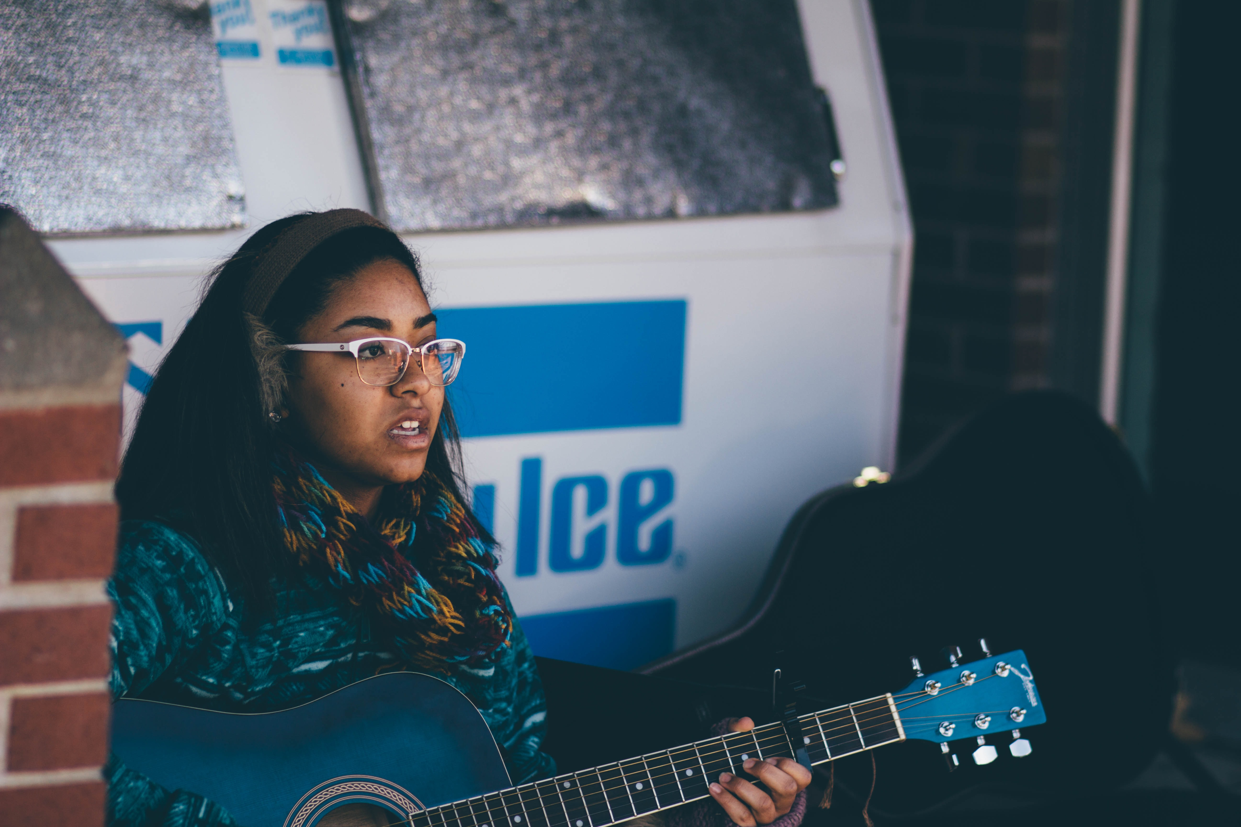 A woman in glasses and earmuffs playing a blue acoustic guitar near a building