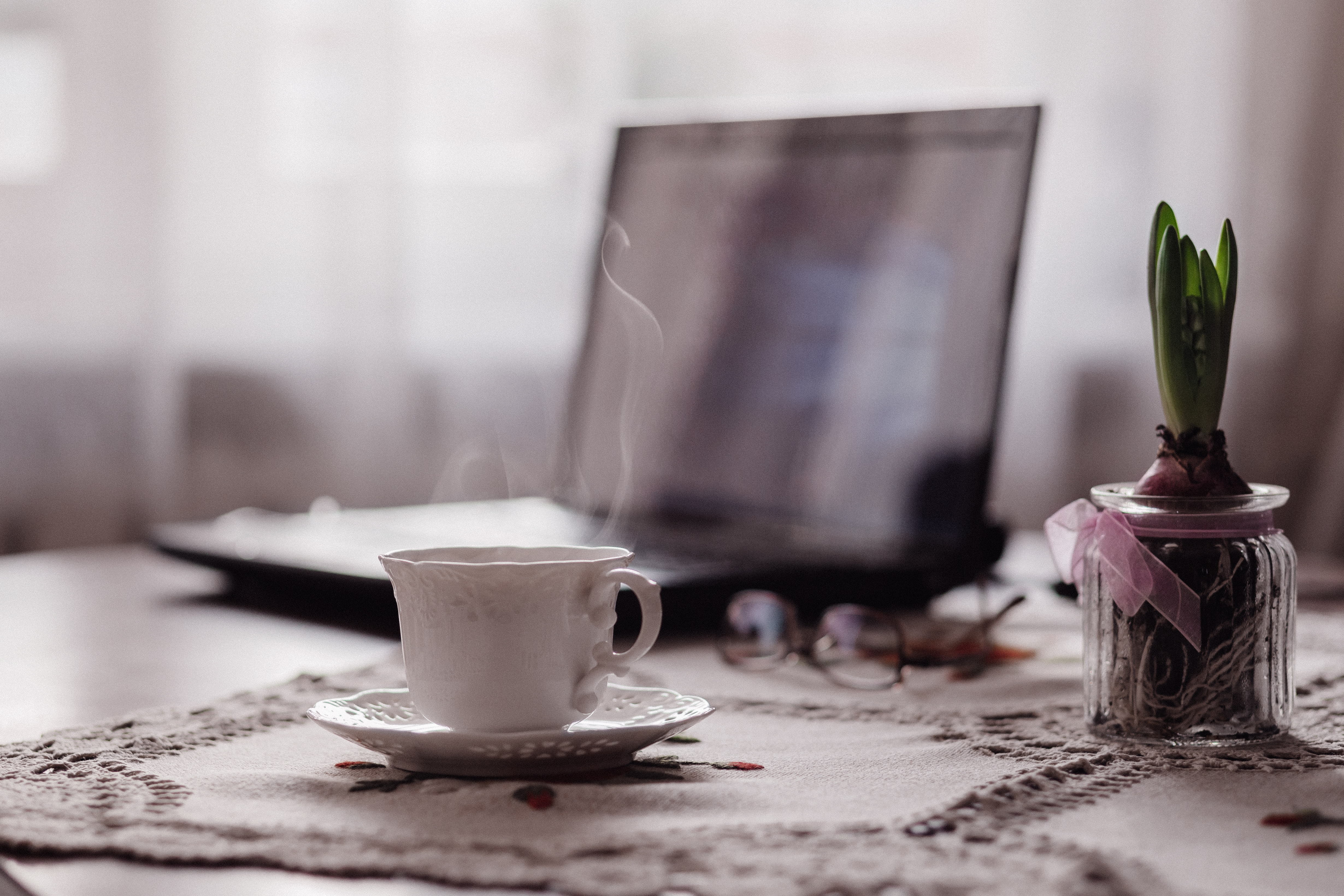 A cup of hot coffee next to a laptop and a potted flower bulb