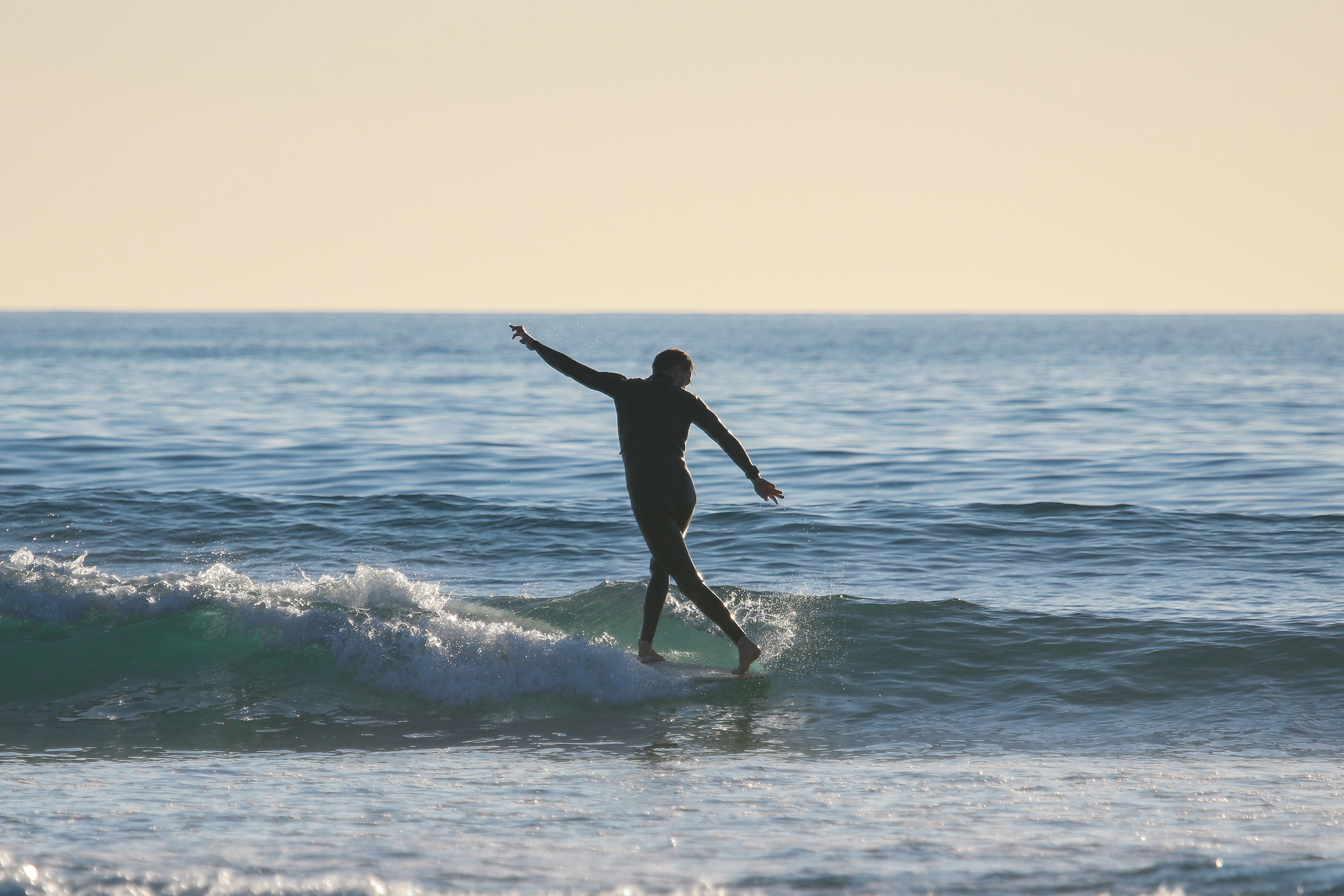 A surfer standing on his board in the sea as small waves break at Carlsbad