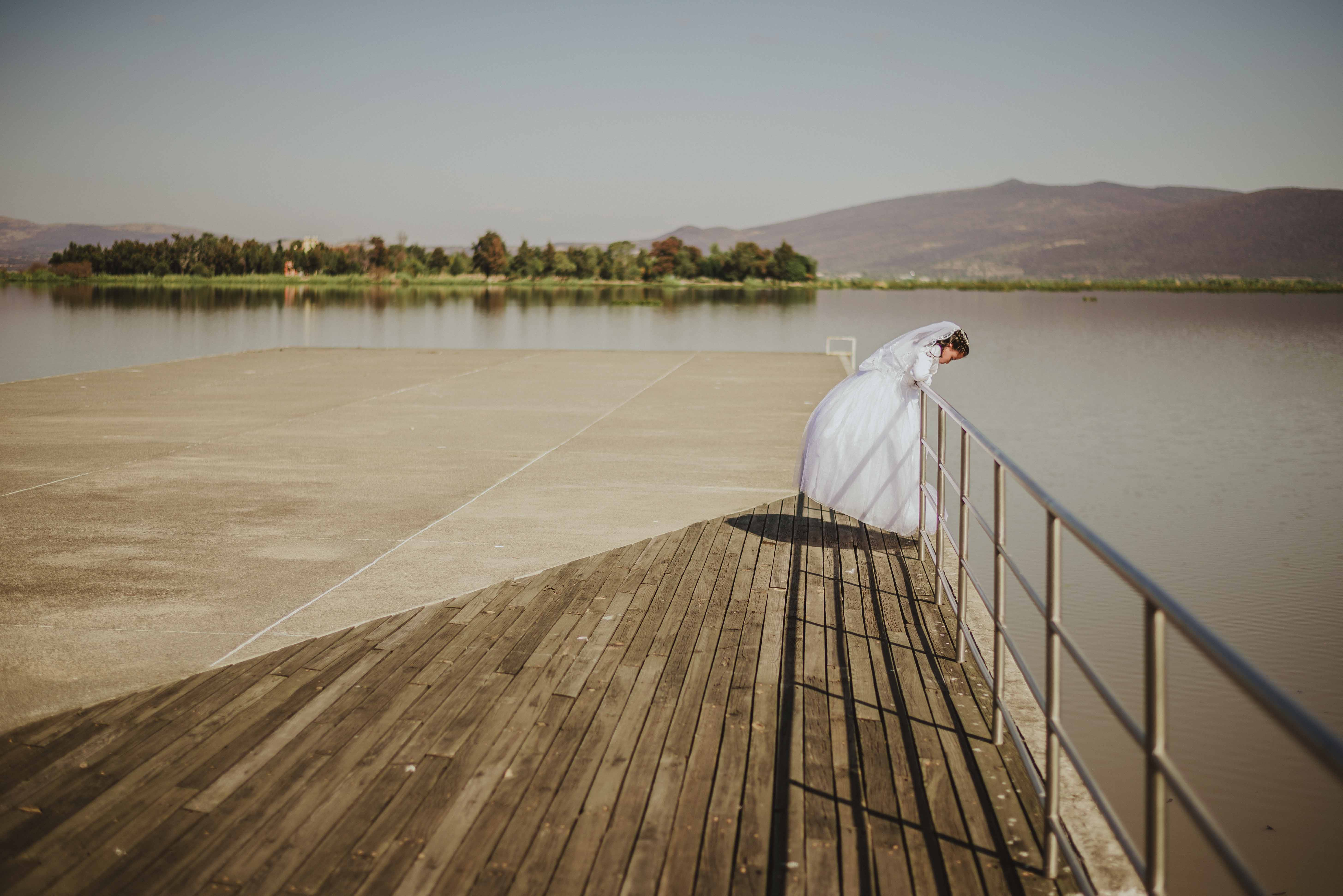 A woman in a wedding dress leans over the railing to look down at the lake, with an island of trees and mountains in the background.