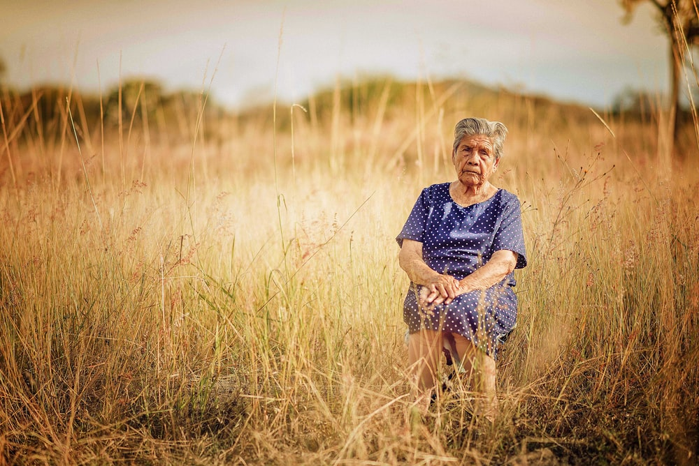 woman sitting on chair and surrounded by grass