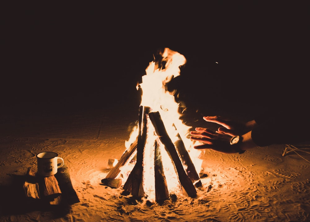 person heating hands beside bonfire at nighttime