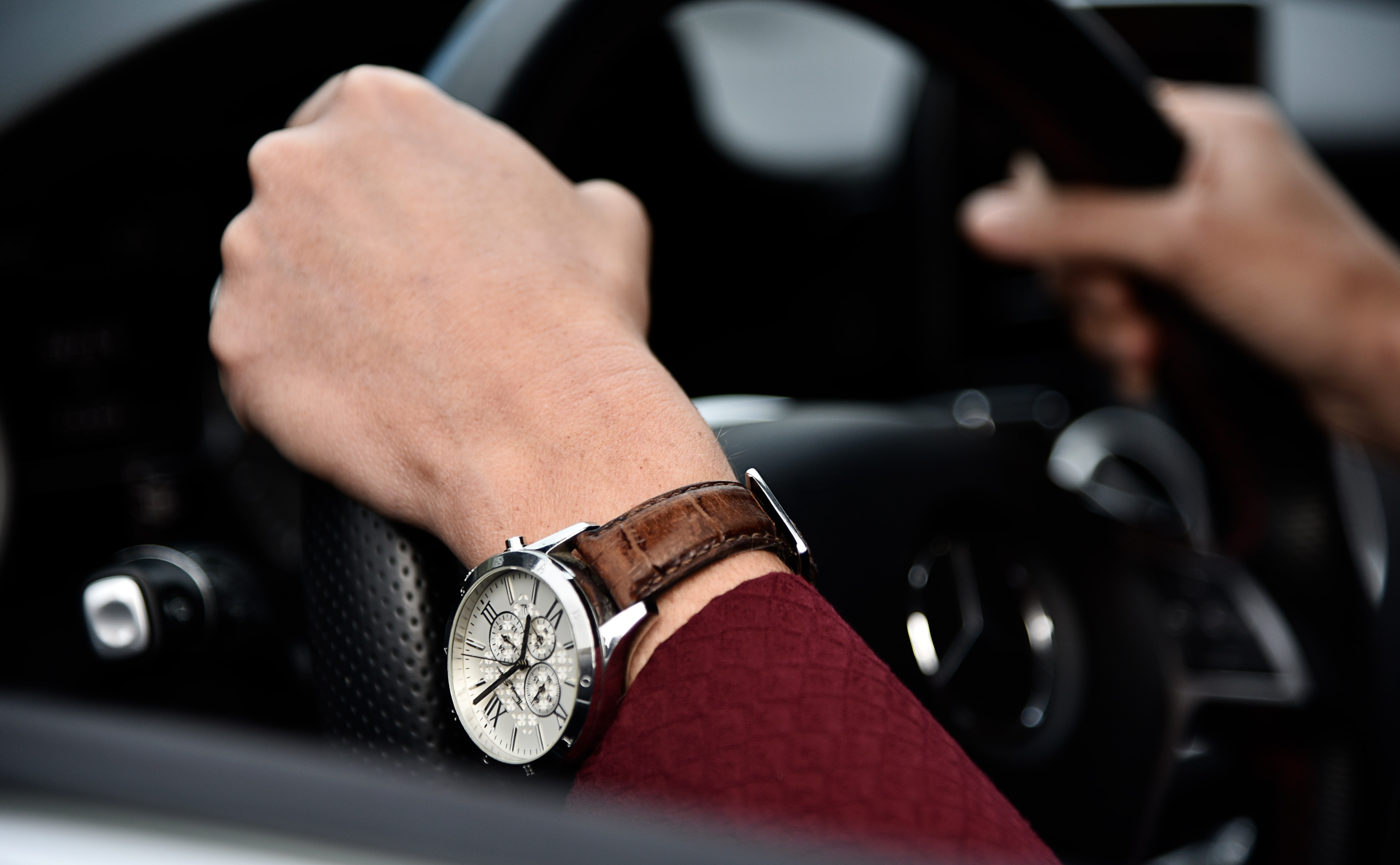 Close up of car steering wheel and male driver's hands wearing watch in Bern