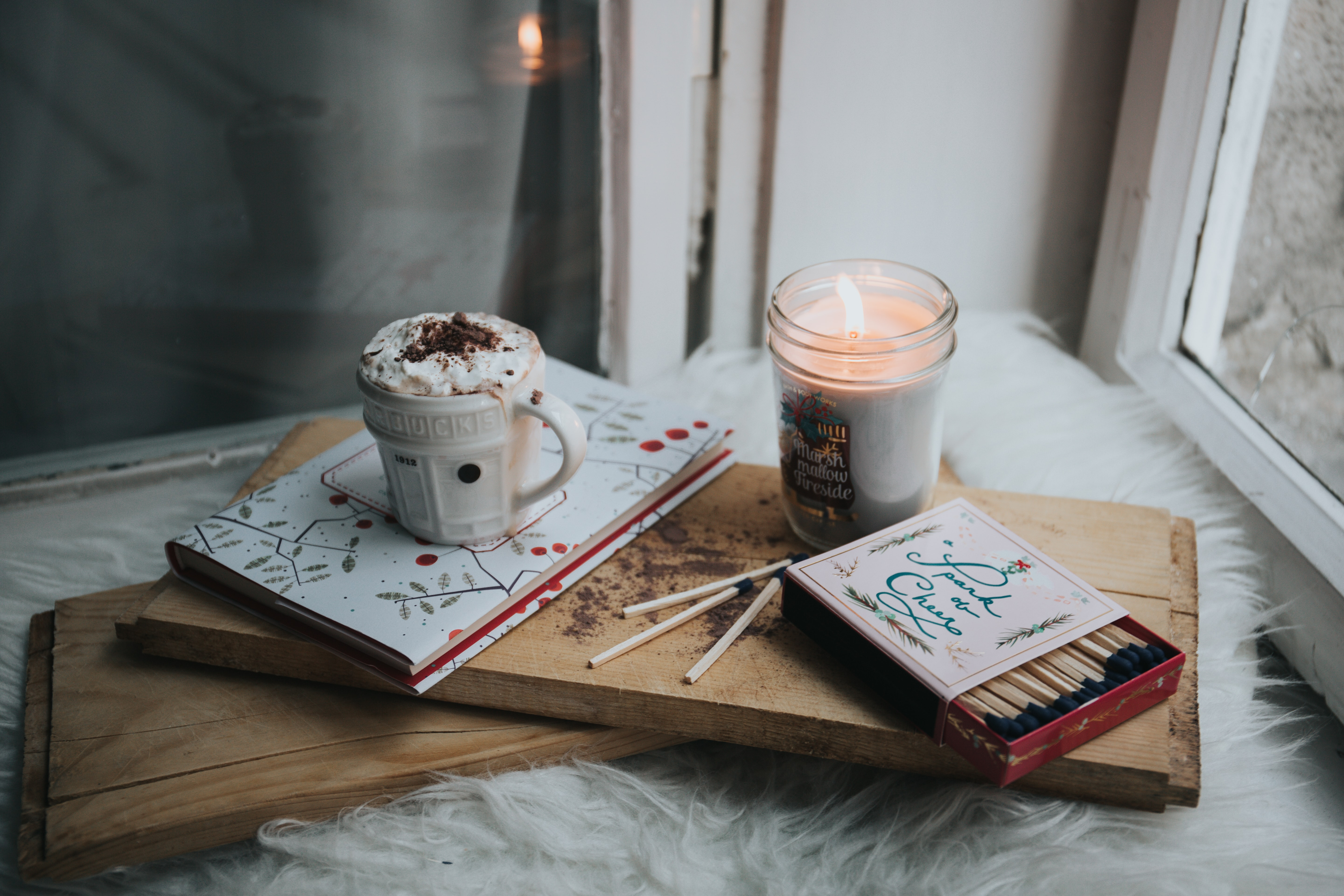 Books on a piece of wood, with a hot drink and candle on top.
