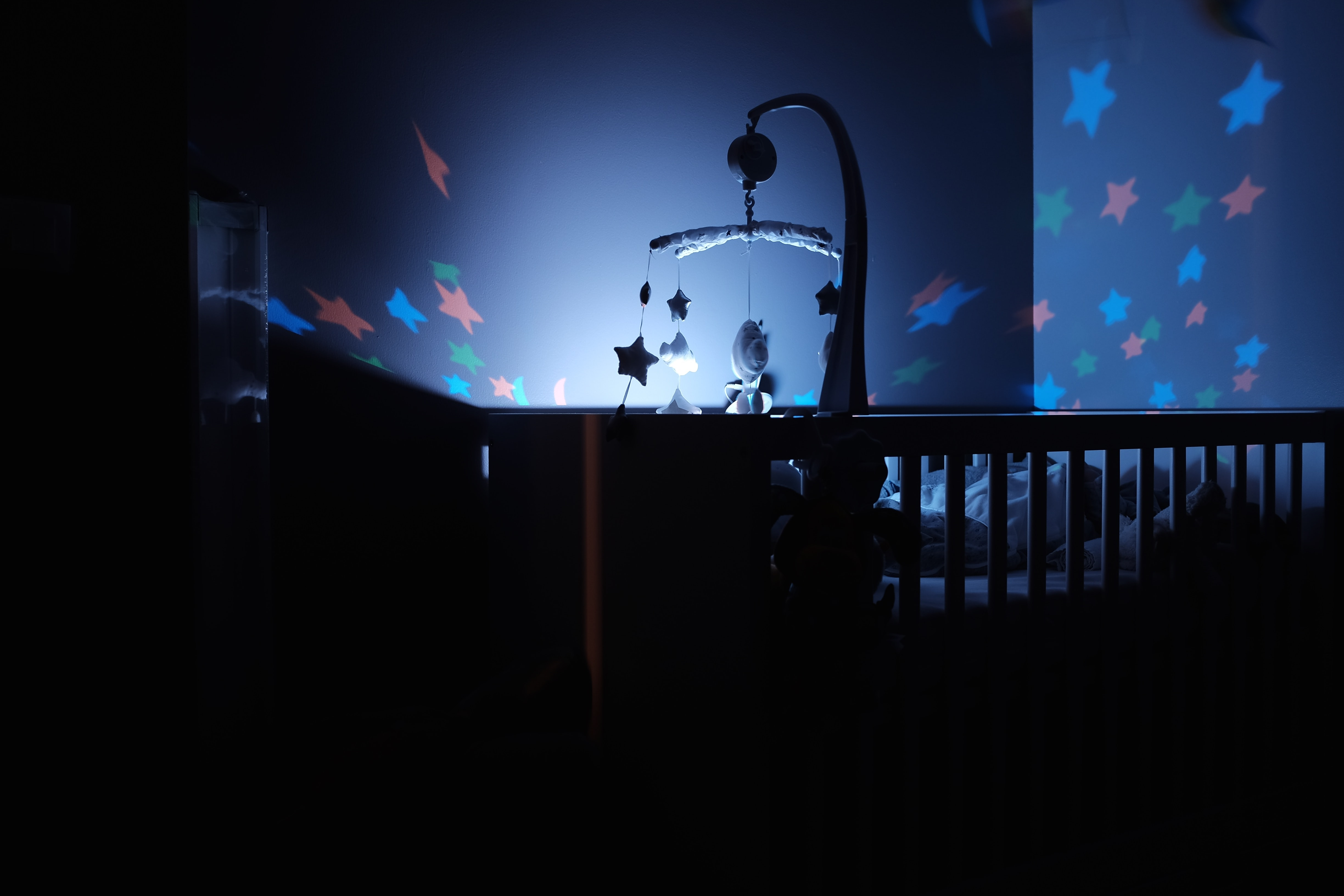 Dark room with a cradle and baby mobile with a night light and stars on the blue walls