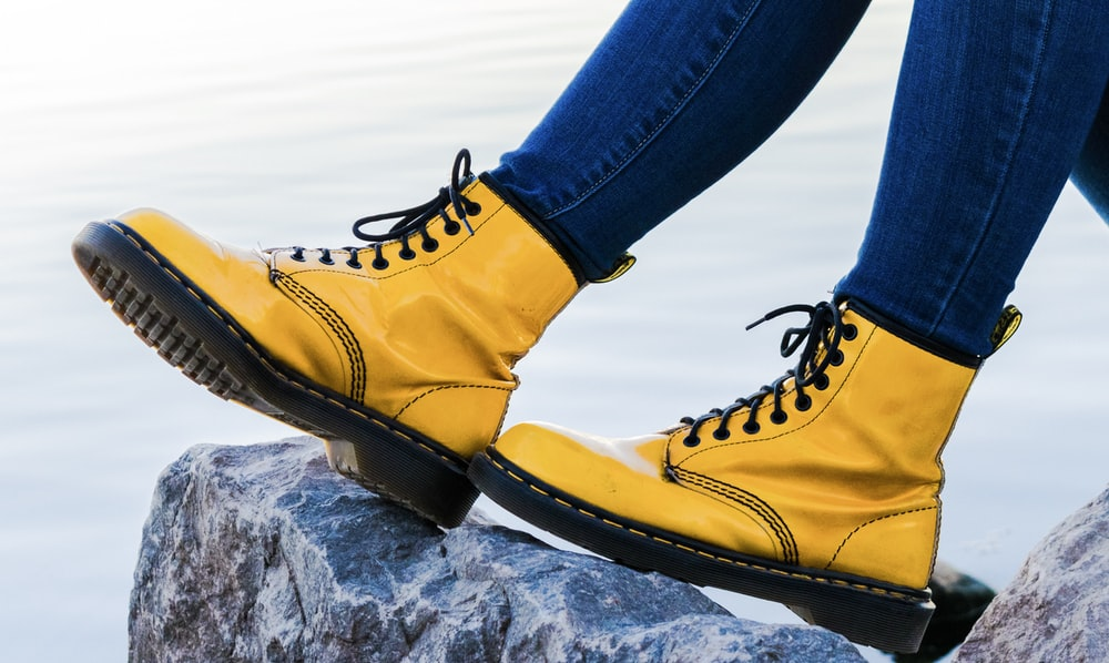 person wearing yellow Doc Martens Airwair boots on gray rock
