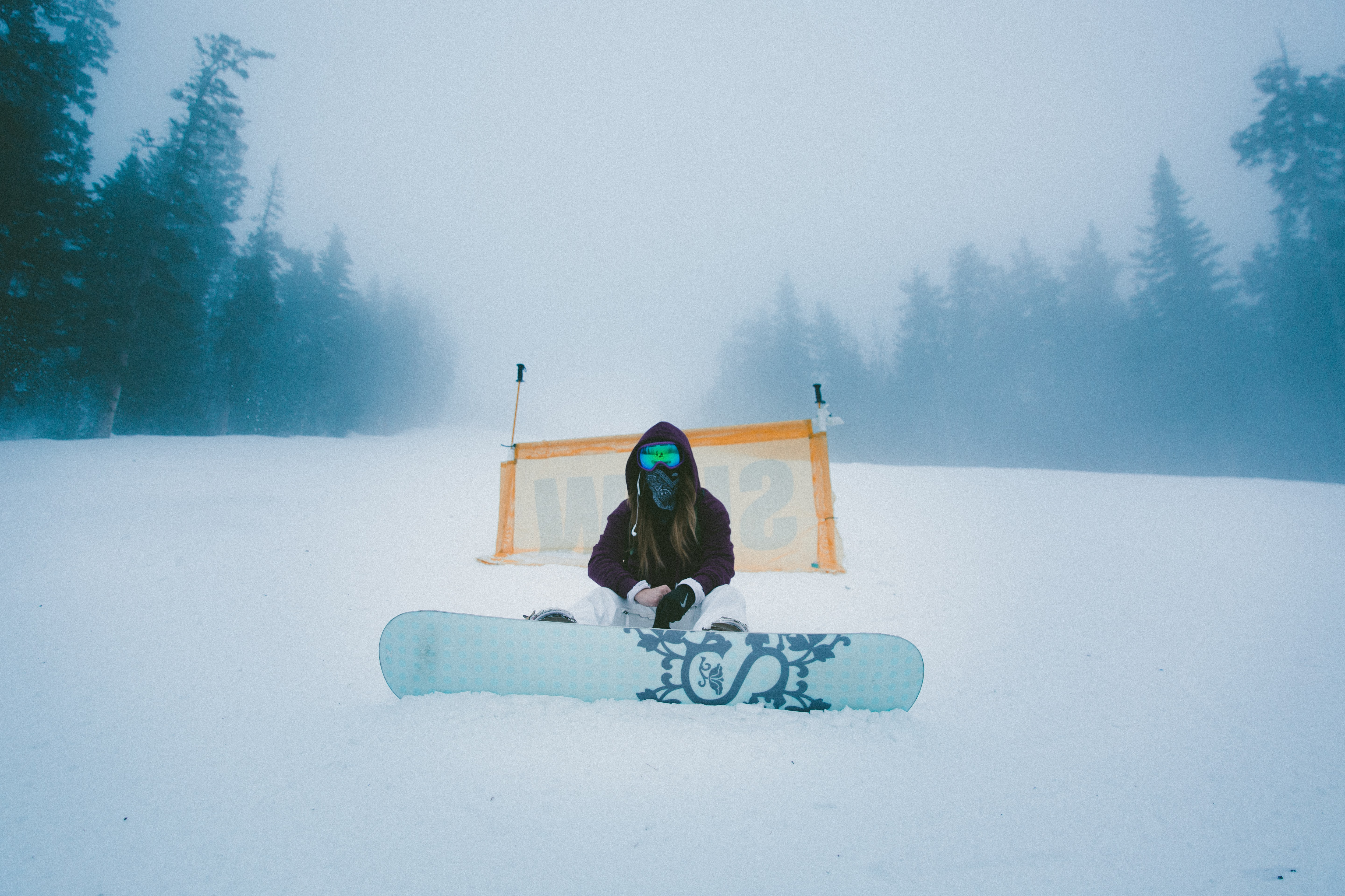 A man sitting with his snowboard at thes starting point on a ski hill
