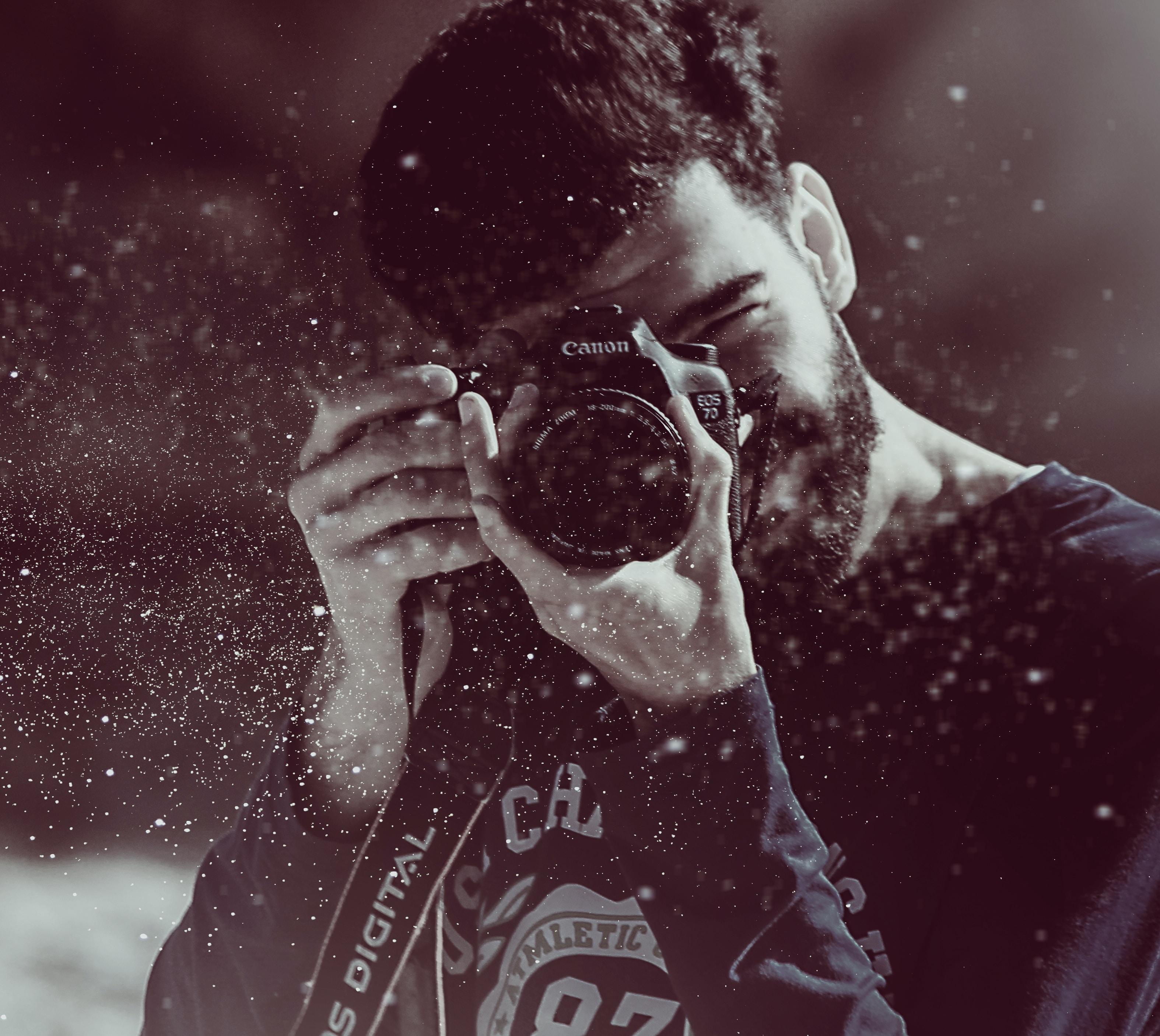 Young dark haired man with beard wearing sweatshirt taking a photo in Asilah