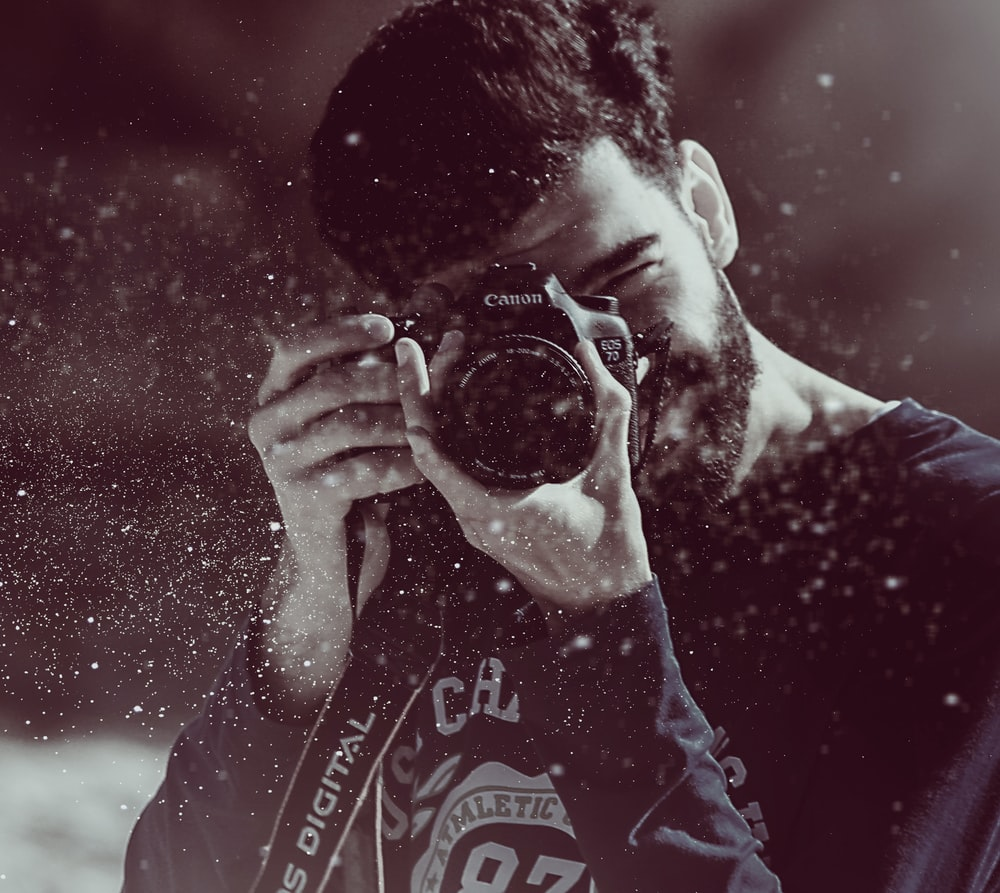 photography of person taking photo using Canon camera