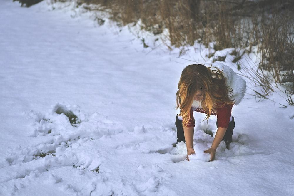woman holding snow near grass