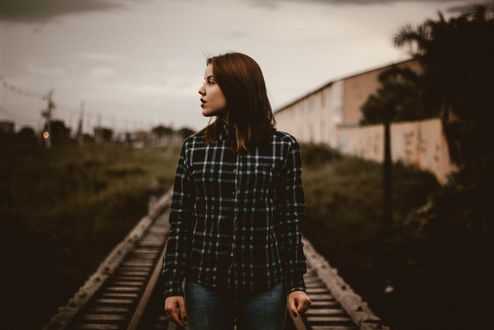 woman standing on train rail track