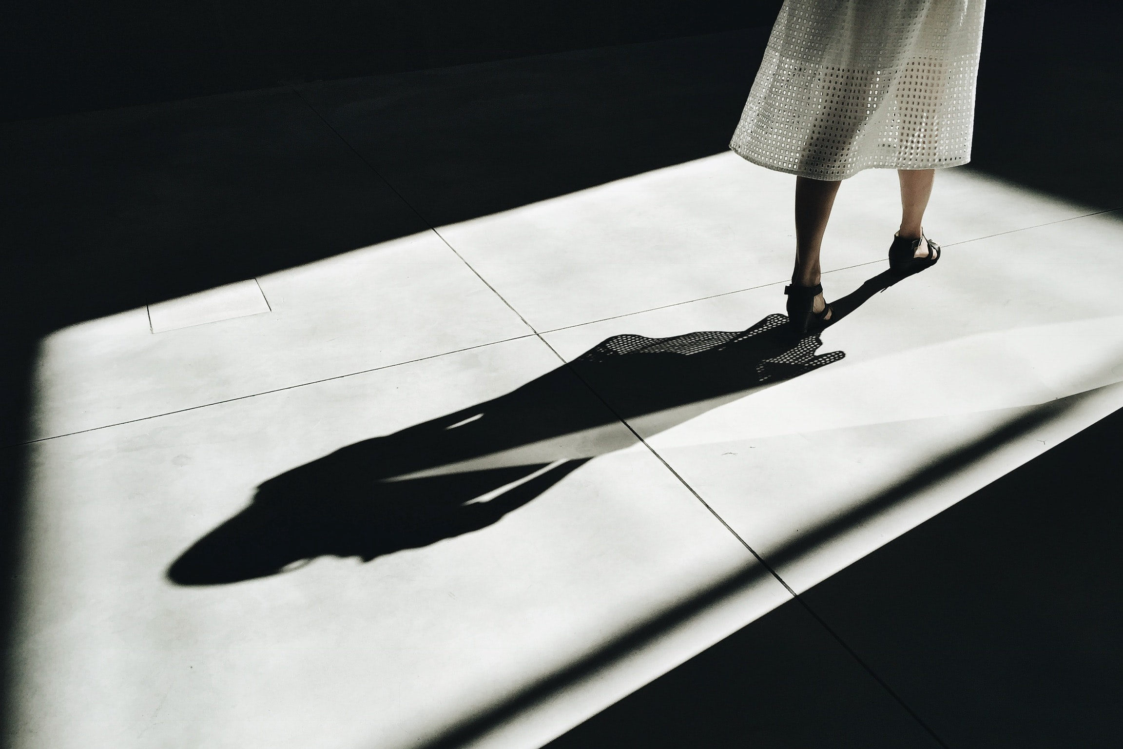 Woman in white dress with black shadow walking in light at Fondazione Prada