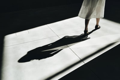 woman walking with shadow shadow zoom background