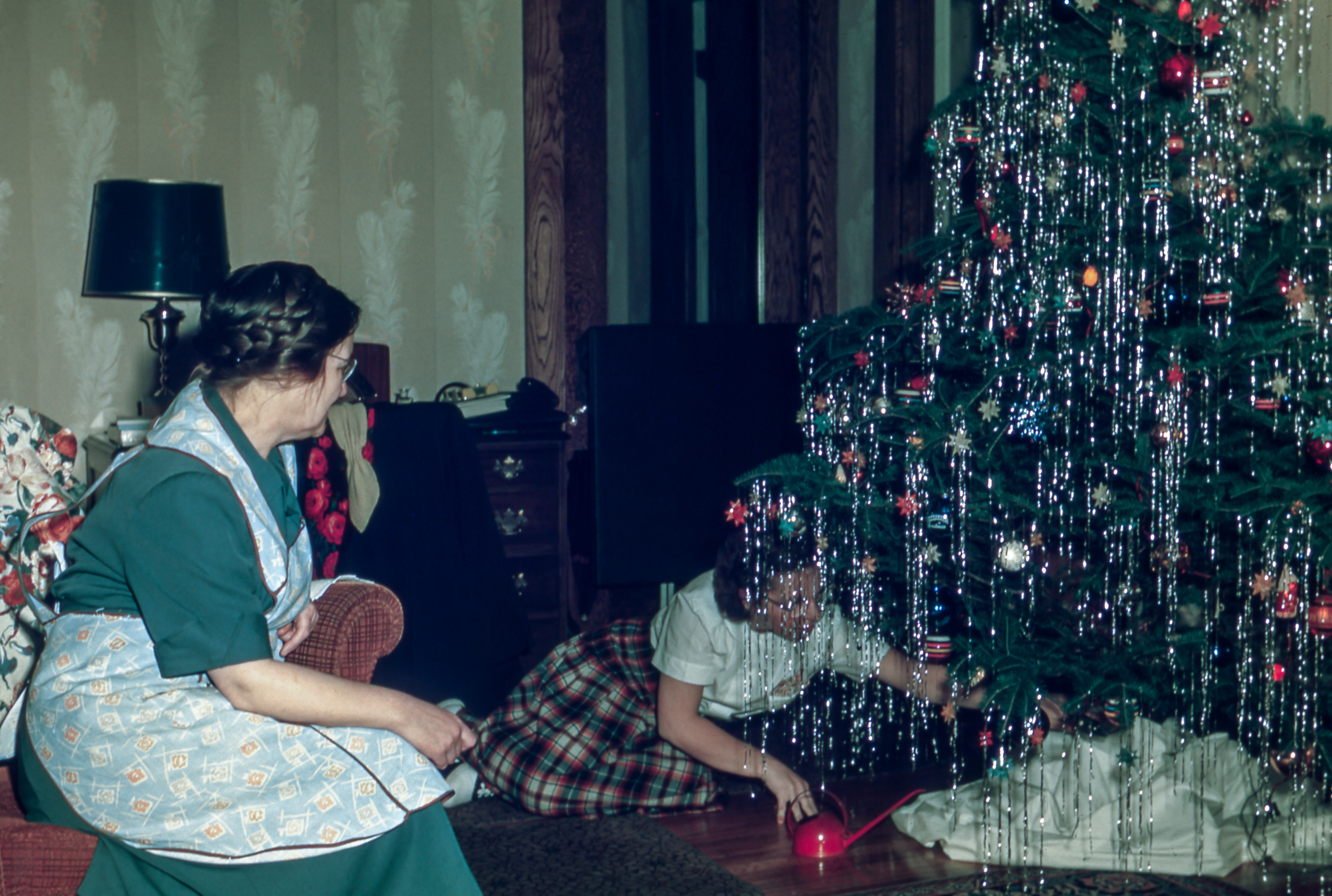 A classic photo of a mom wearing a pinafore and glasses, sitting on a chair watching her daughter put gifts under a Christmas tree