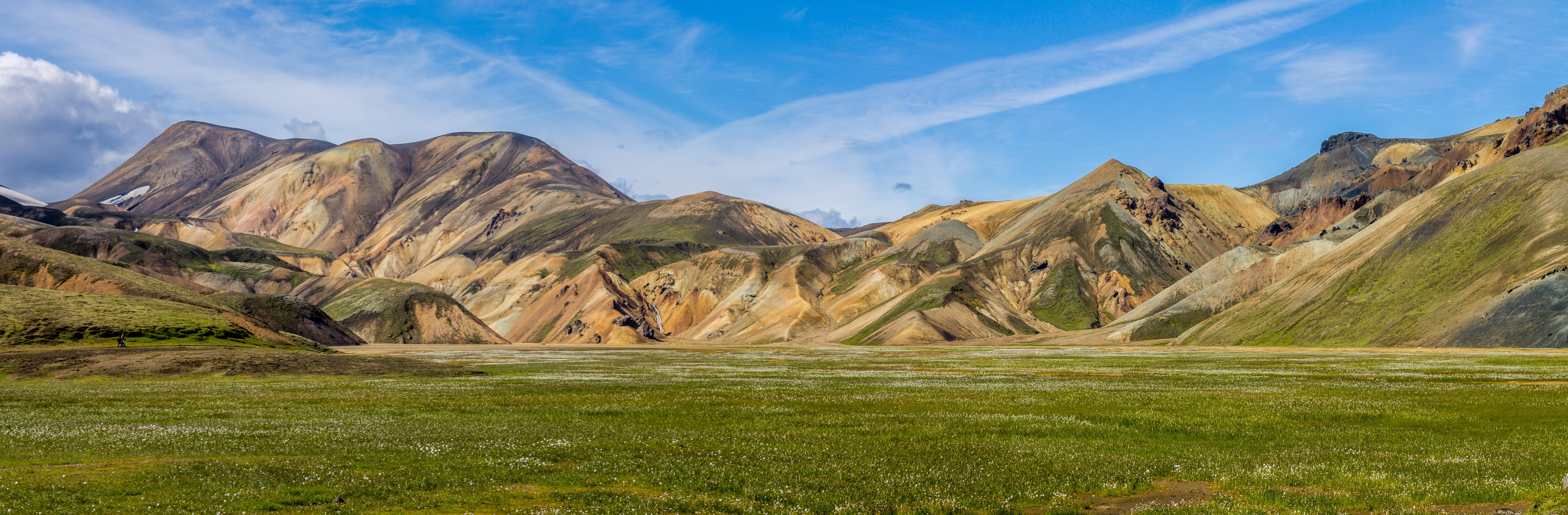 green grass under brown mountain hill during daytime