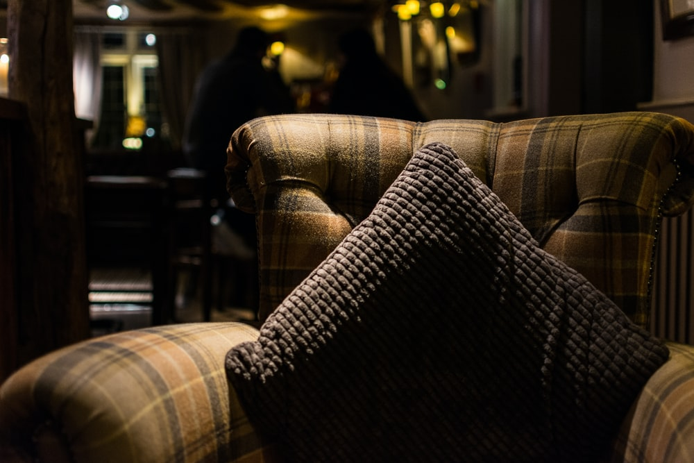 closeup photo of gray throw pillow on tufted sofa chair