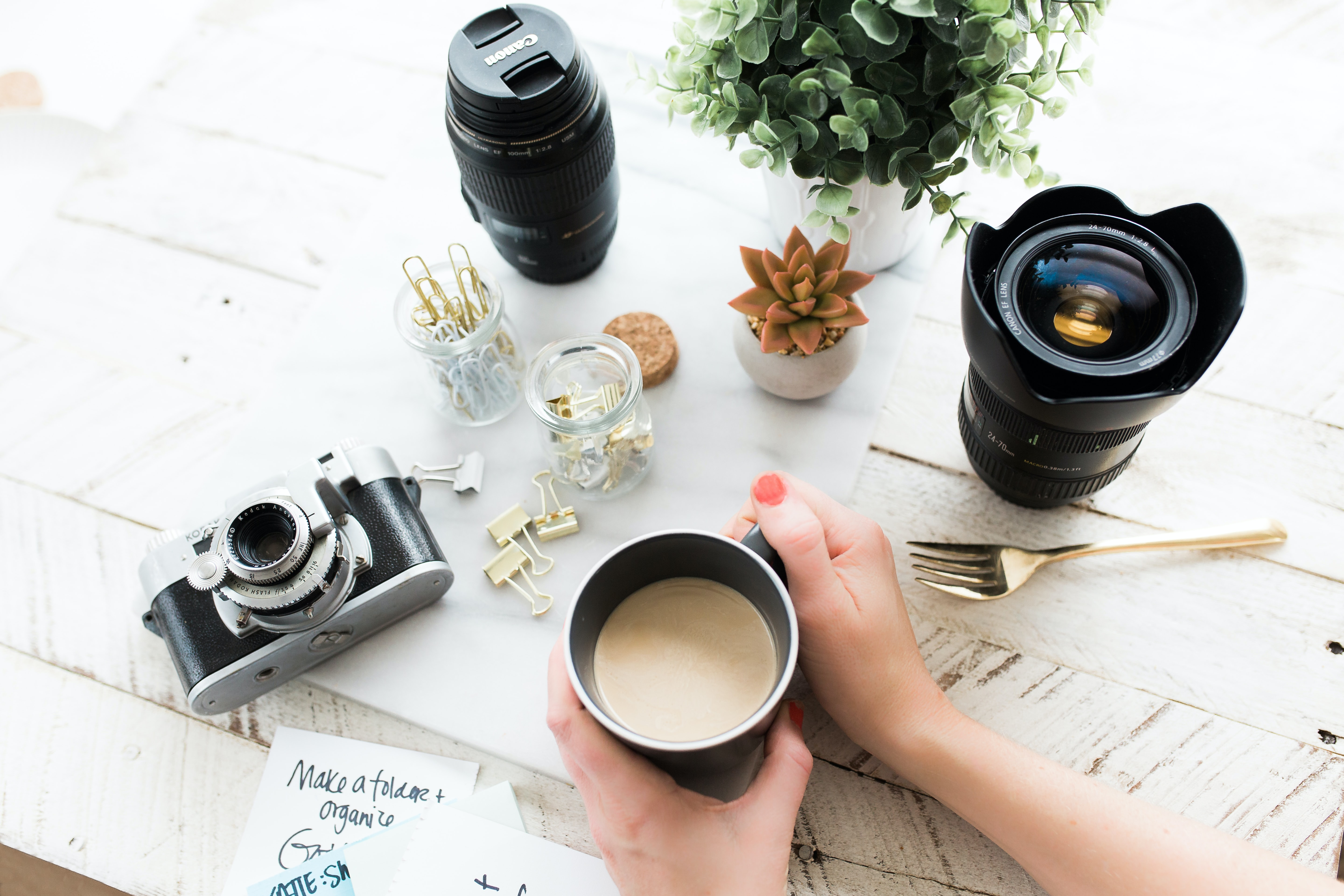 person holding black ceramic coffee mug beside black DSLR camera