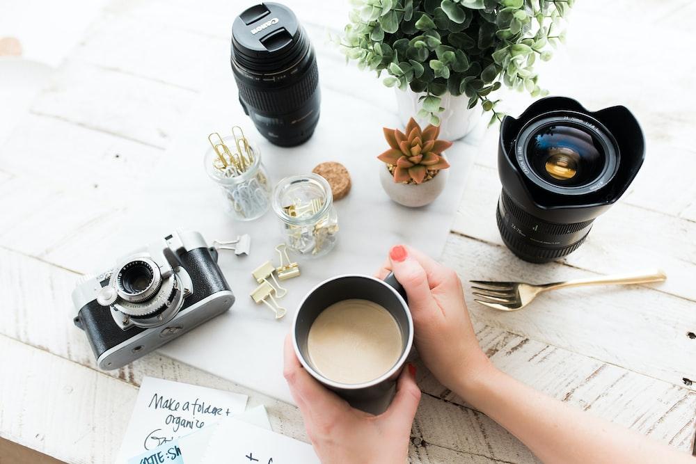 person holding black ceramic coffee mug beside black DSLR camera
