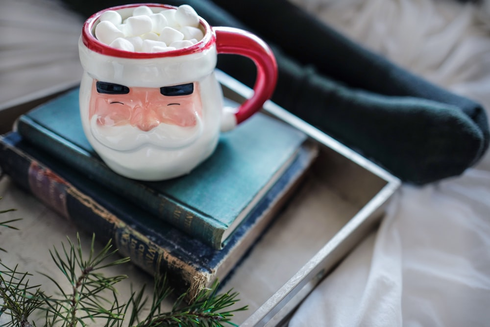 white and red ceramic mug on books