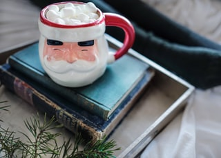 white and red ceramic mug on books