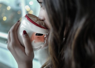 woman drinking on white and red ceramic mug