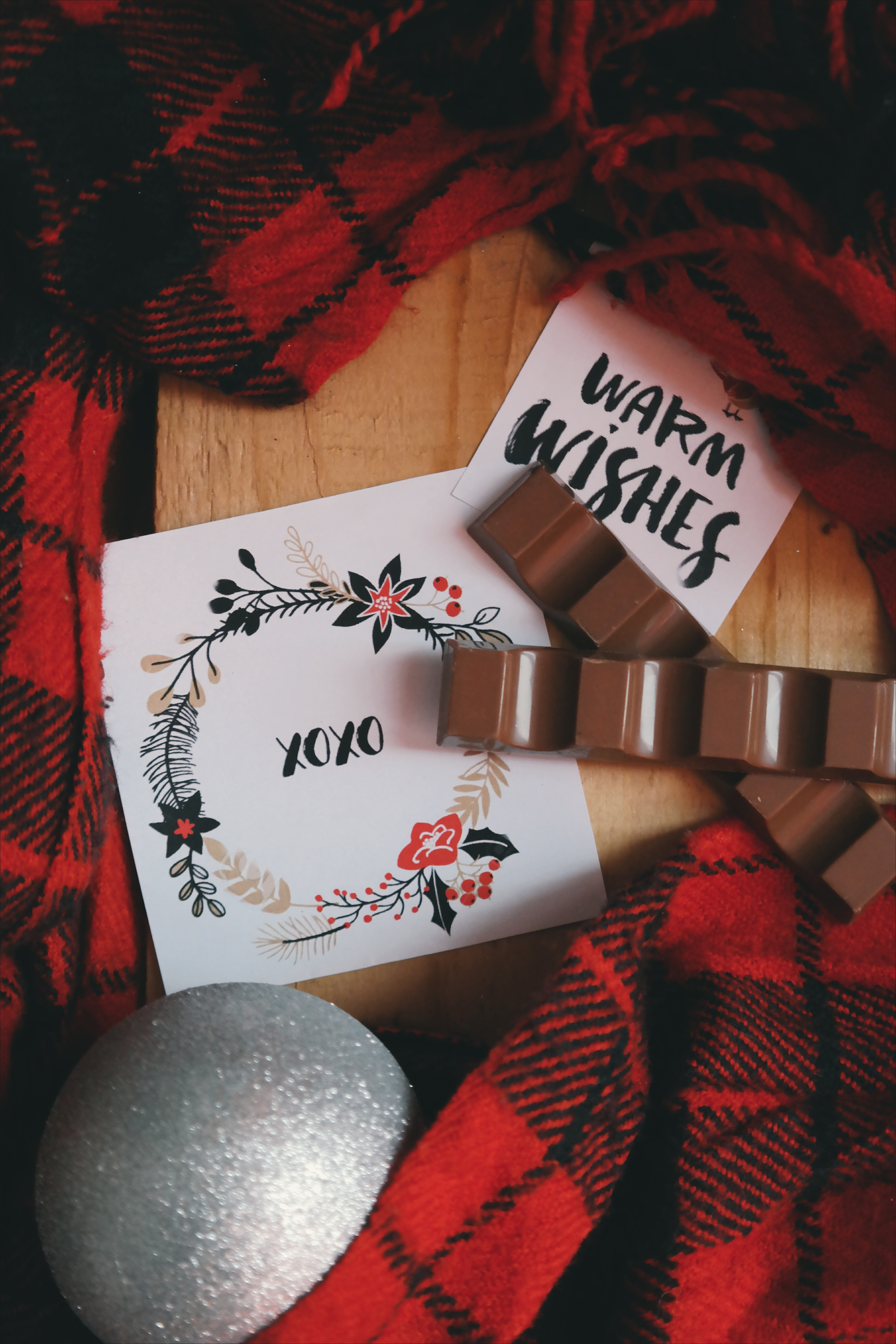 An XOXO note next to a gray Christmas ornament and red plaid fabric.