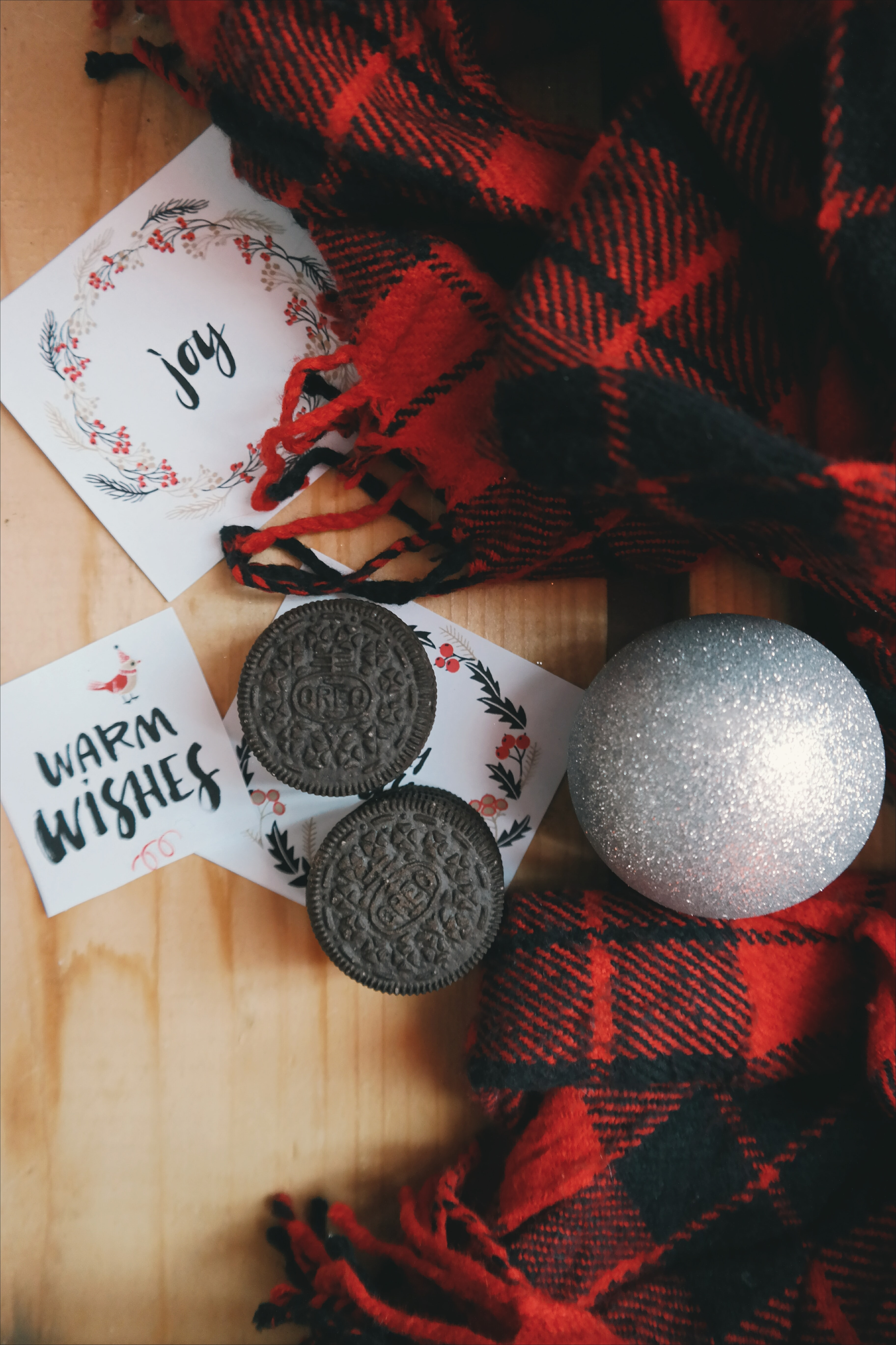 Oreo cookies around Christmas paper notes, an ornament and red plaid fabric.