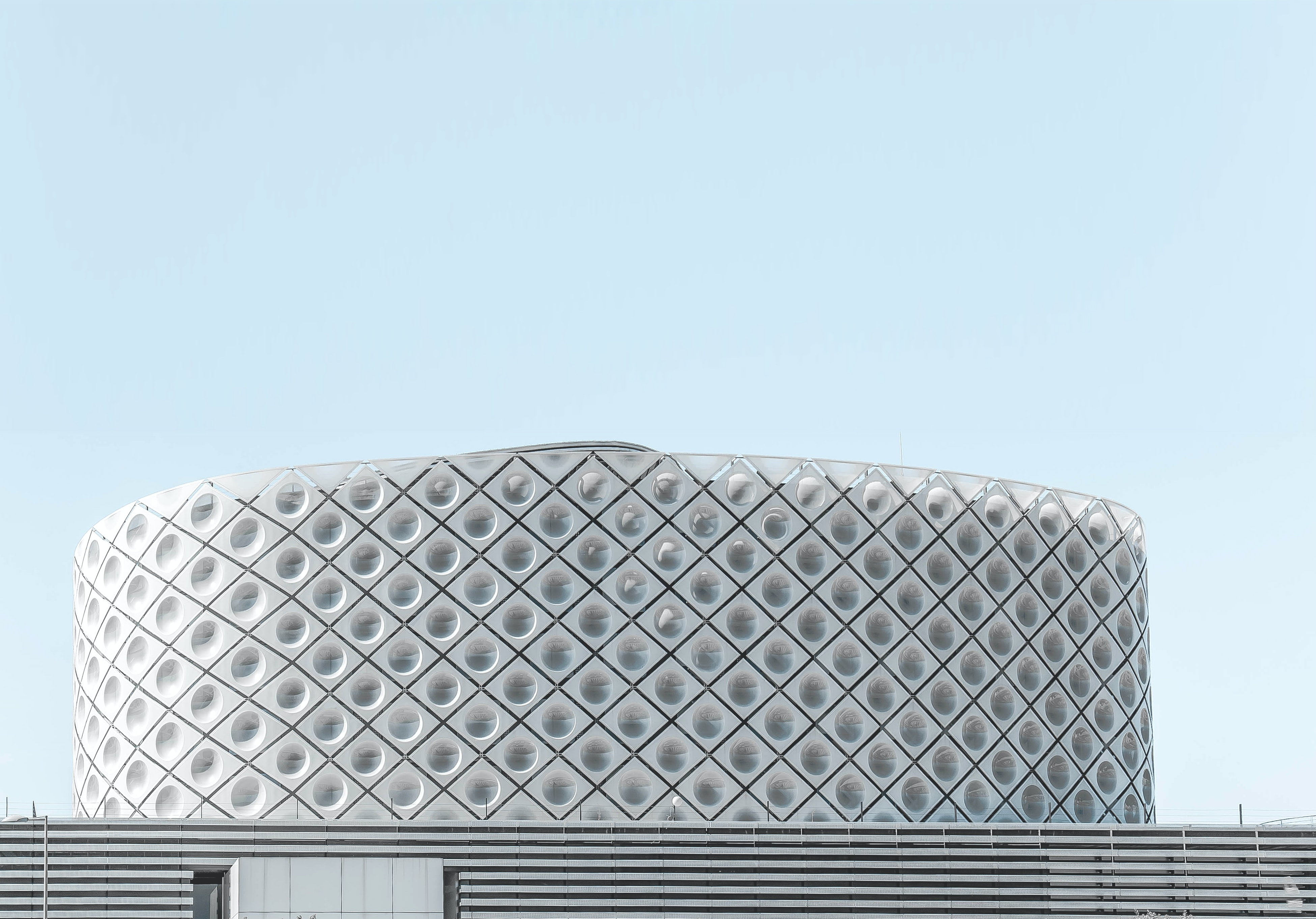 A circular arena with a dotted pattern on its white facade in Madrid