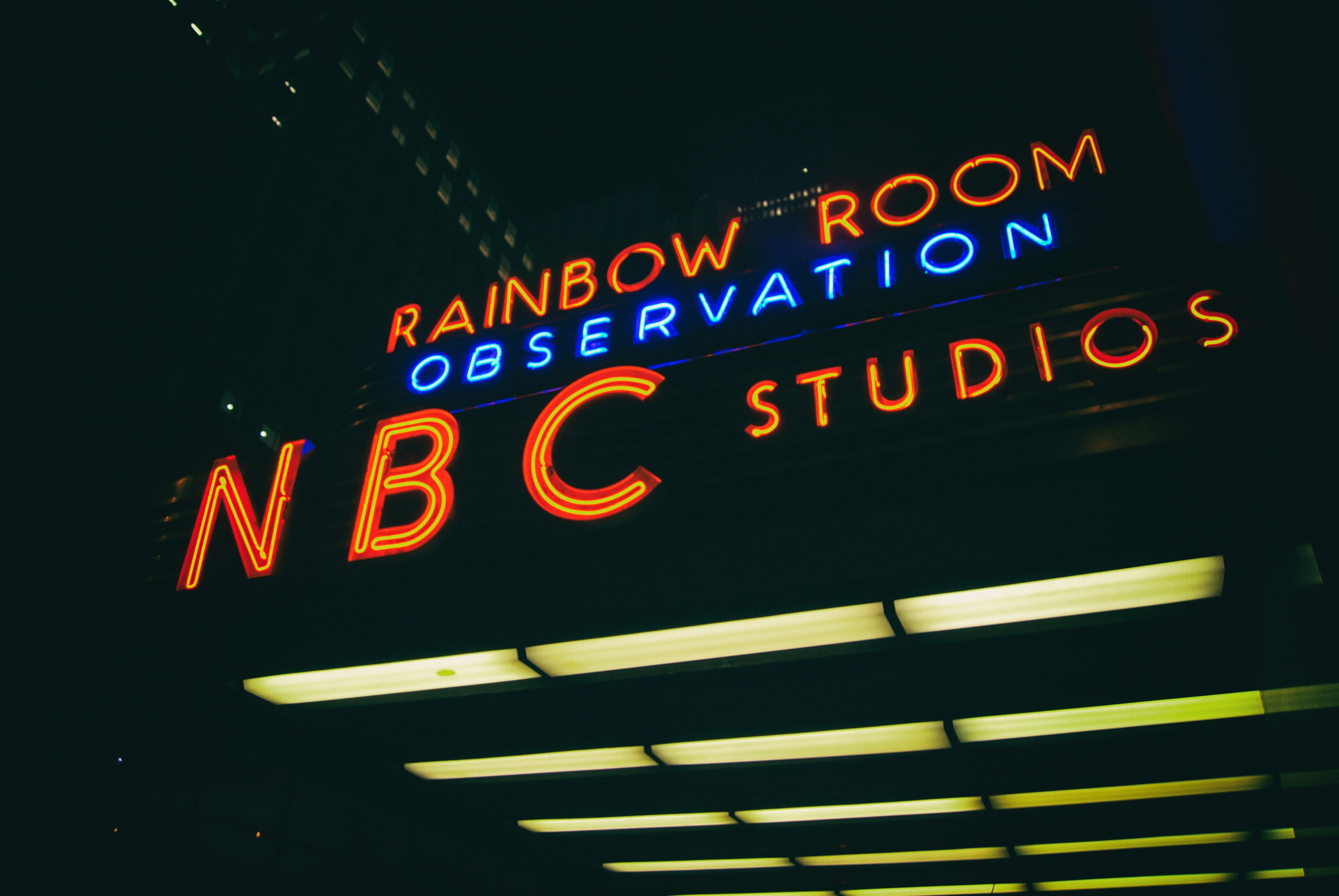 Glowing NBC Studios blue and red neon sign on building in New York City