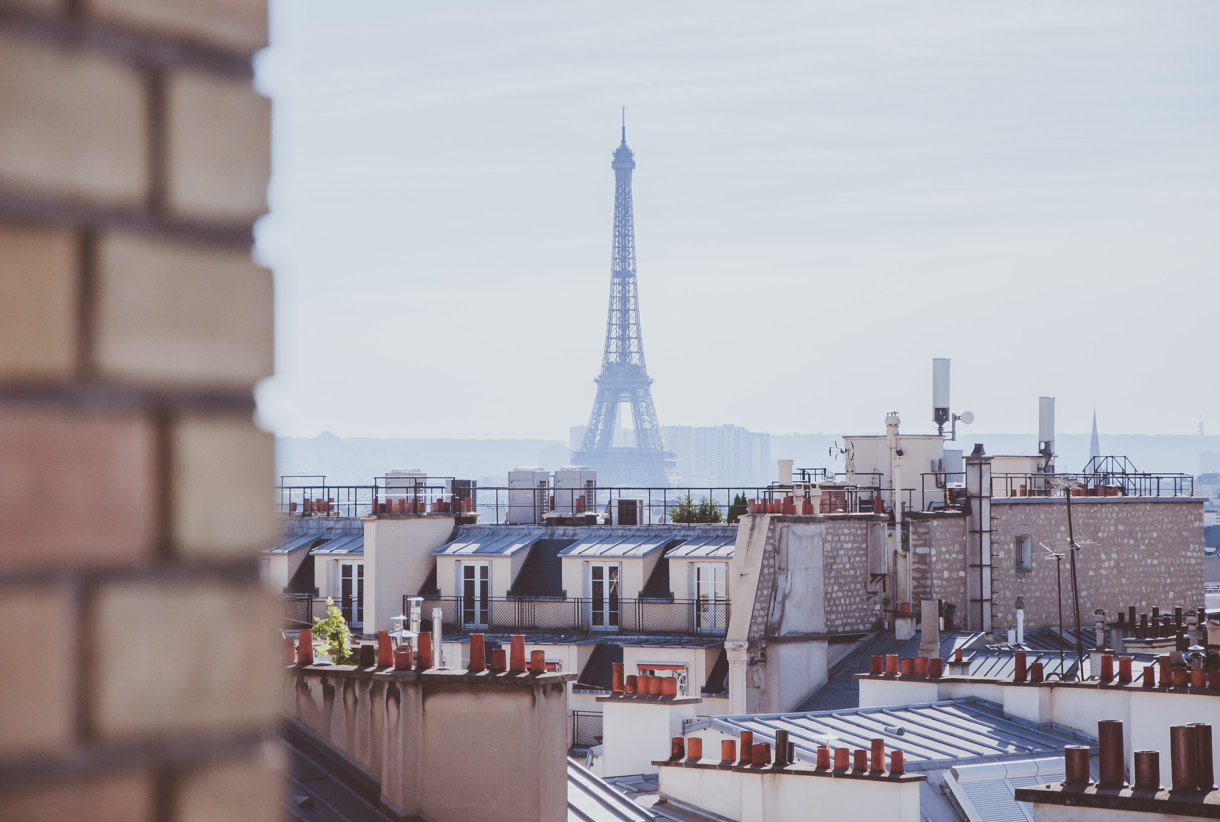 A rooftop view of brick chimney, buildings, and the Eiffel Tower in Paris, France.