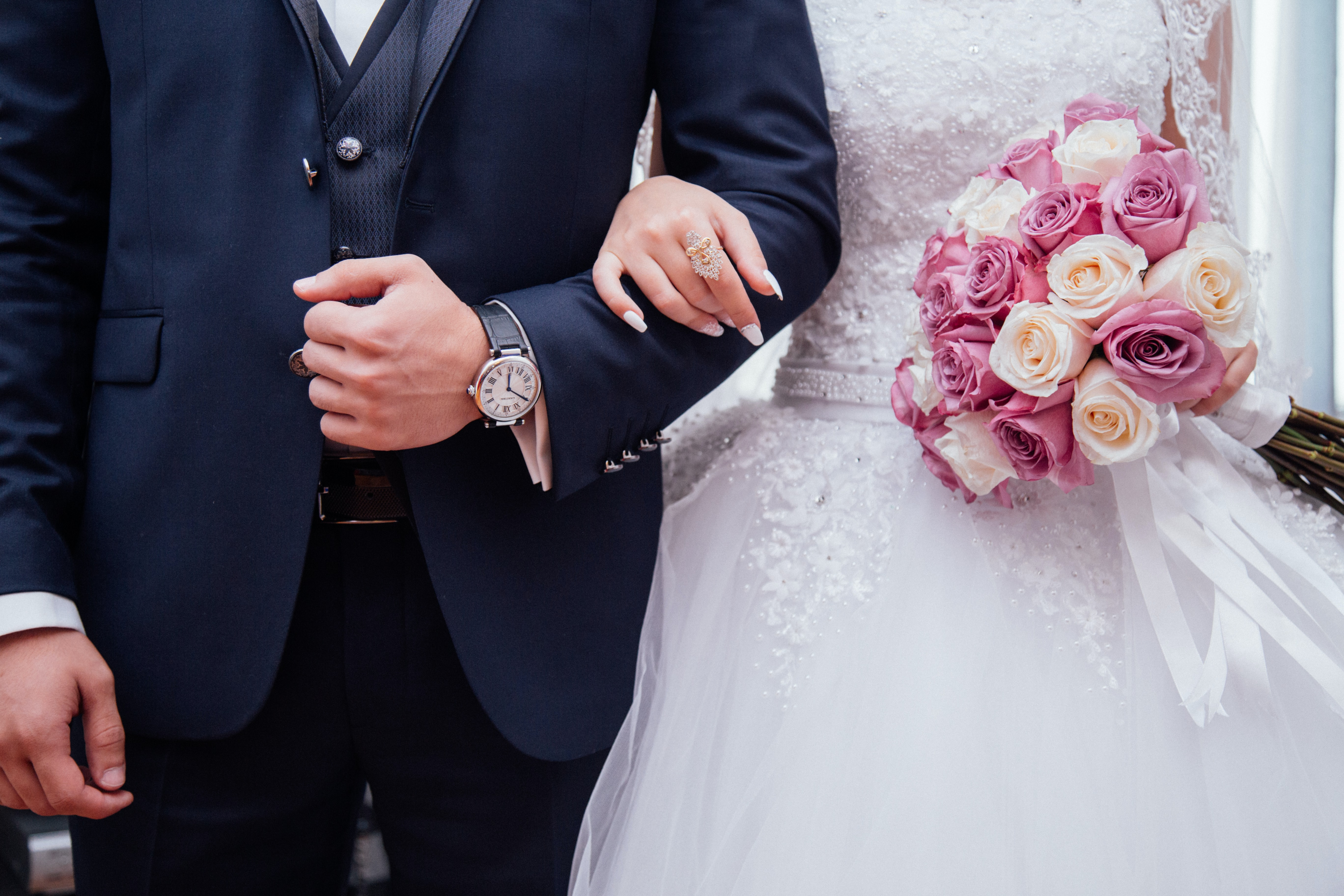 A bride holding a pink and white roses bouquet while holding arms with her husband.