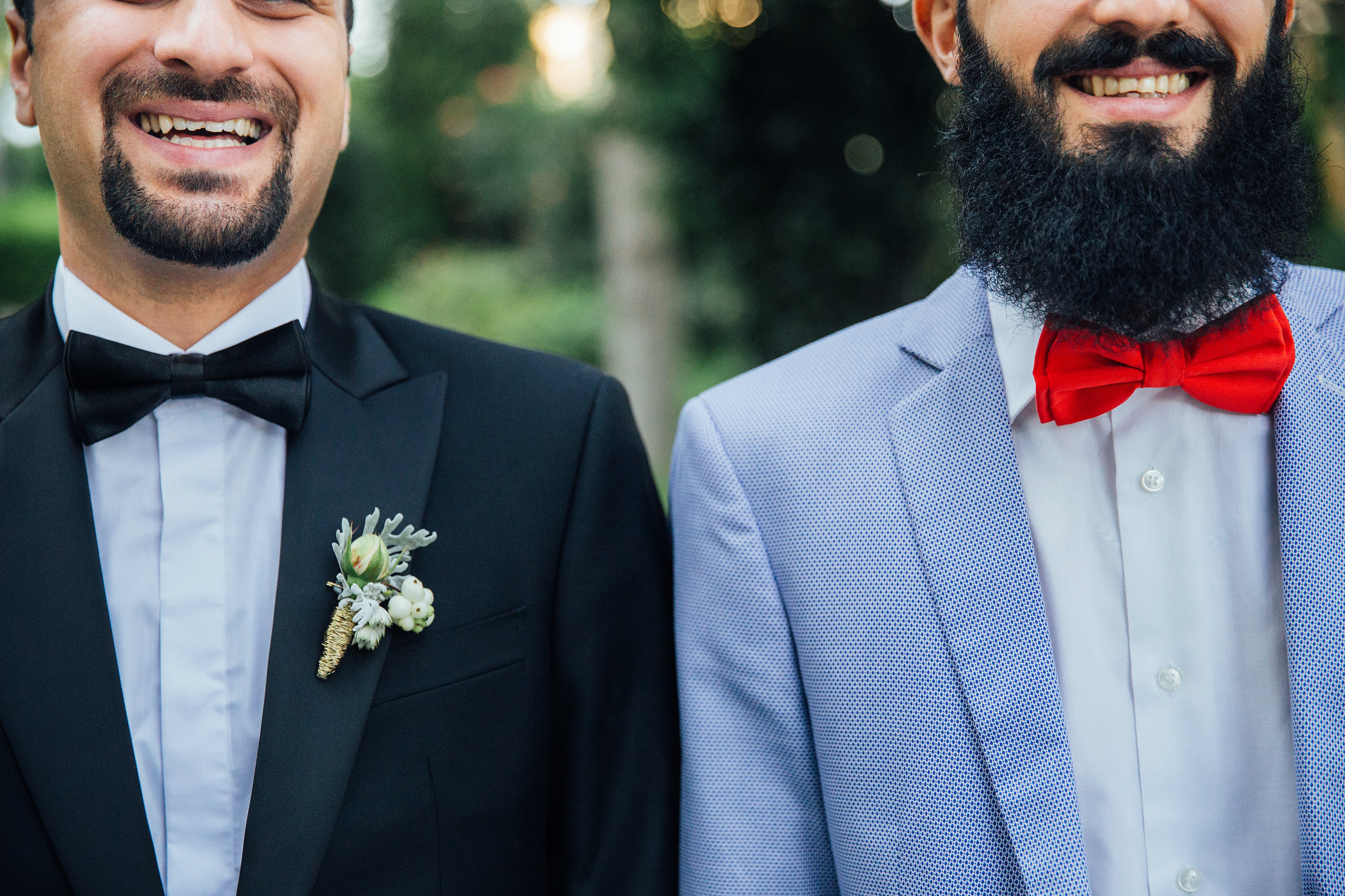 Two smiling bearded men in suits and bowties stand together outdoors
