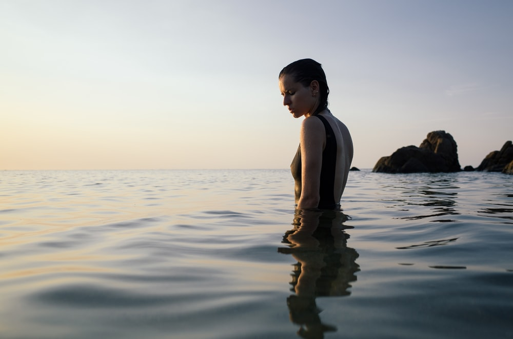 photo of woman on sea during daytime