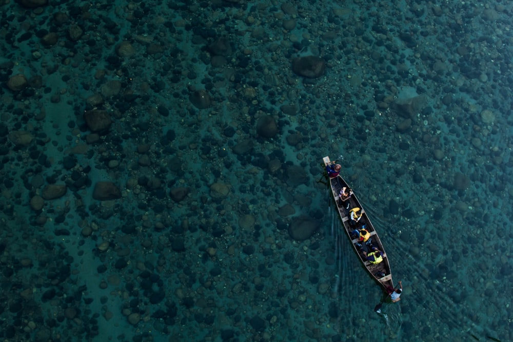 aerial photo of canoe on calm water with people