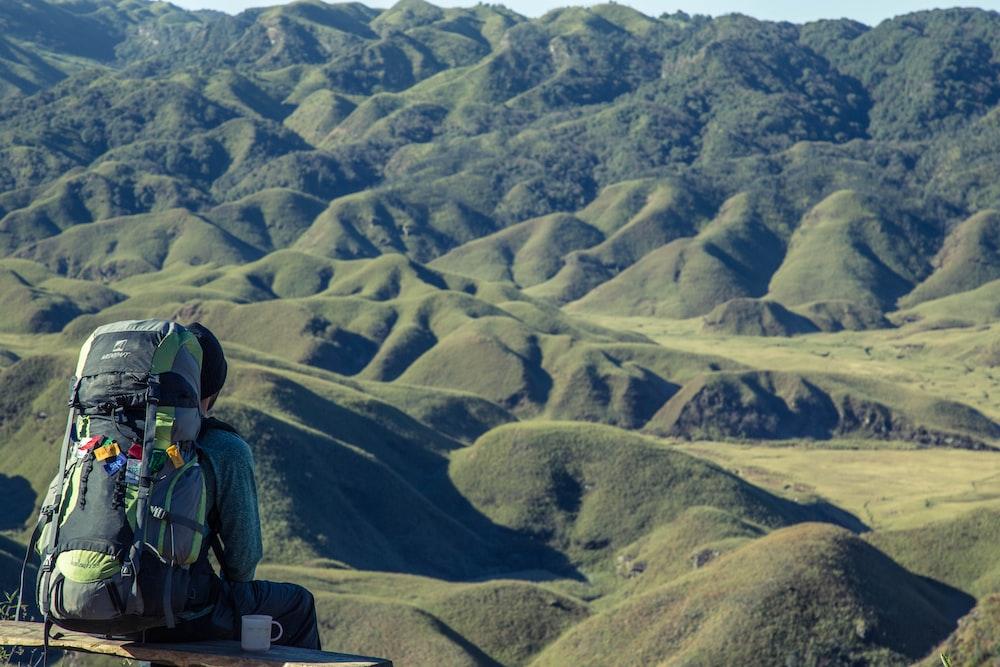 man sitting looking at mountains
